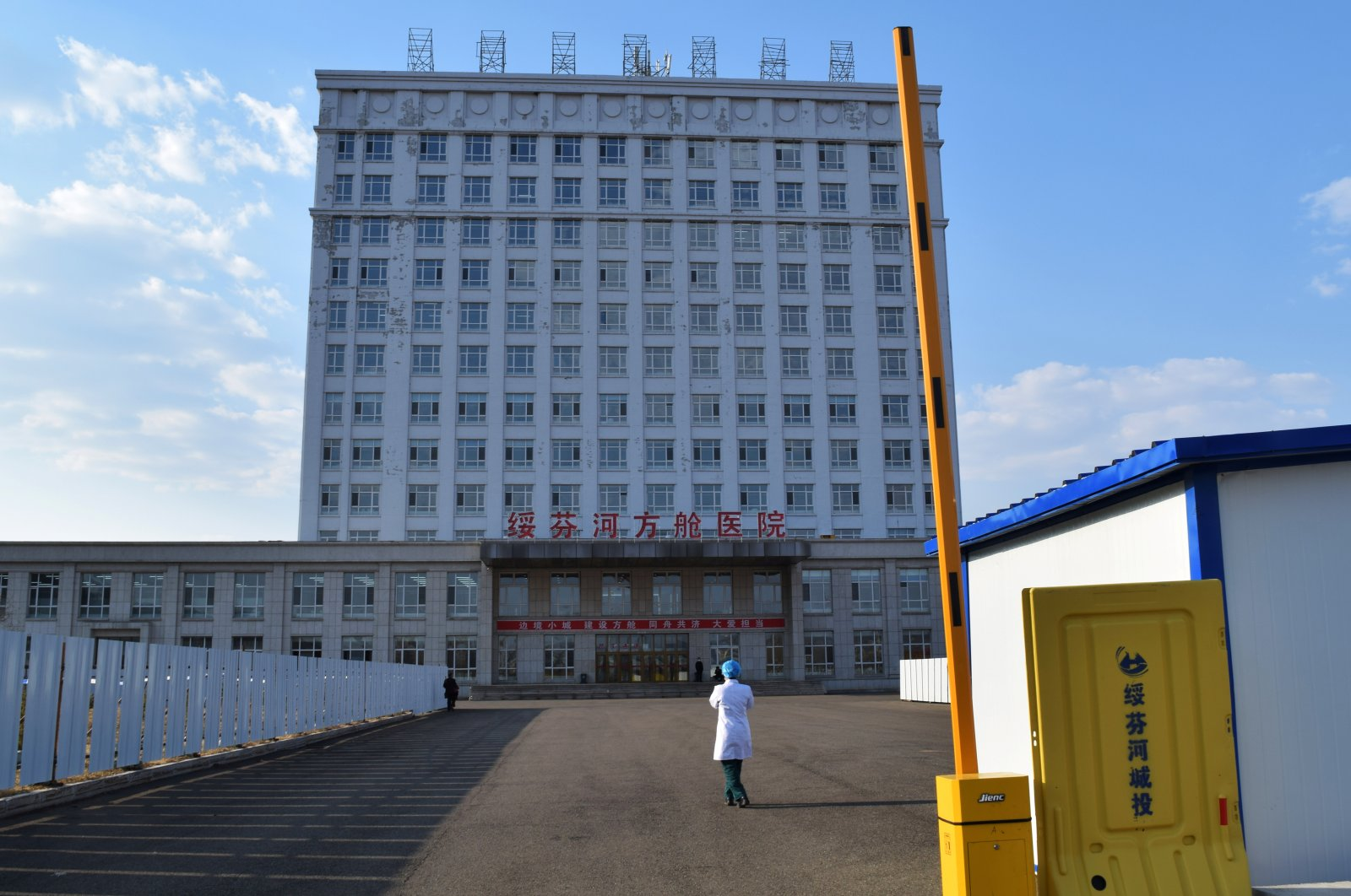 A medical worker is seen outside a makeshift hospital, which was converted from an office building, to treat patients with COVID-19 in Suifenhe, a city in Heilongjiang province on China's border with Russia, April 13, 2020. (REUTERS Photo)