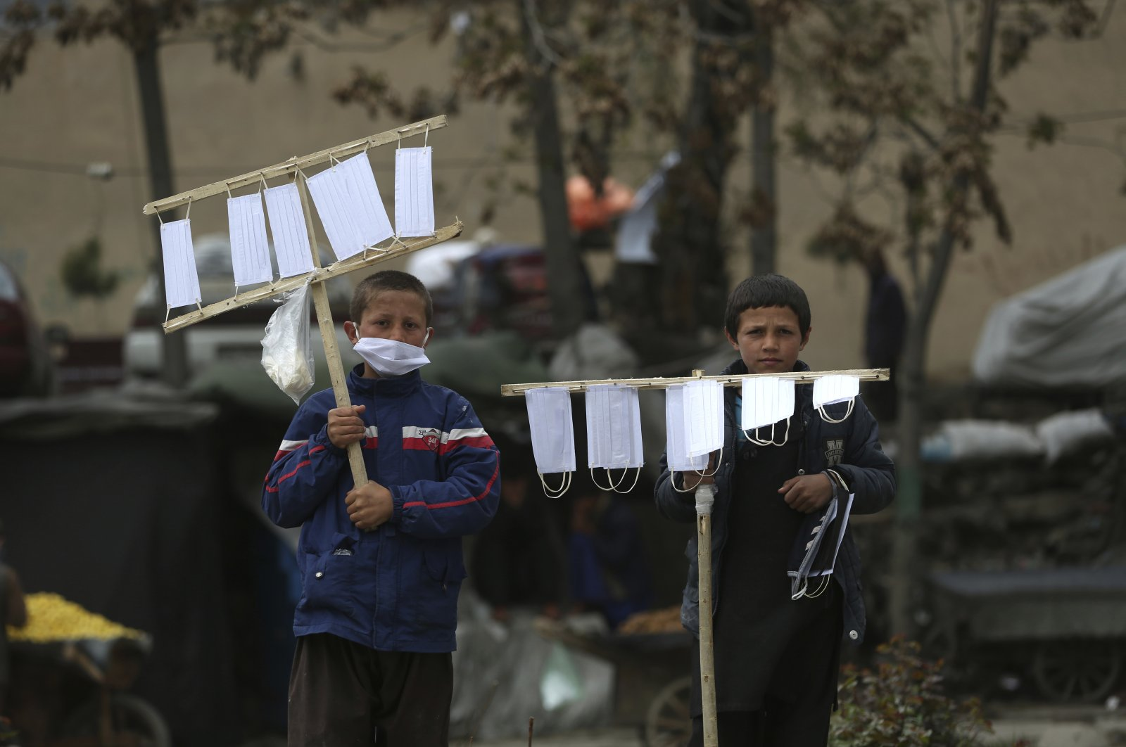 Street vendors selling protective masks to help curb the spread of the coronavirus wait for customers in Kabul, Afghanistan, Tuesday, April 14, 2020. (AP)