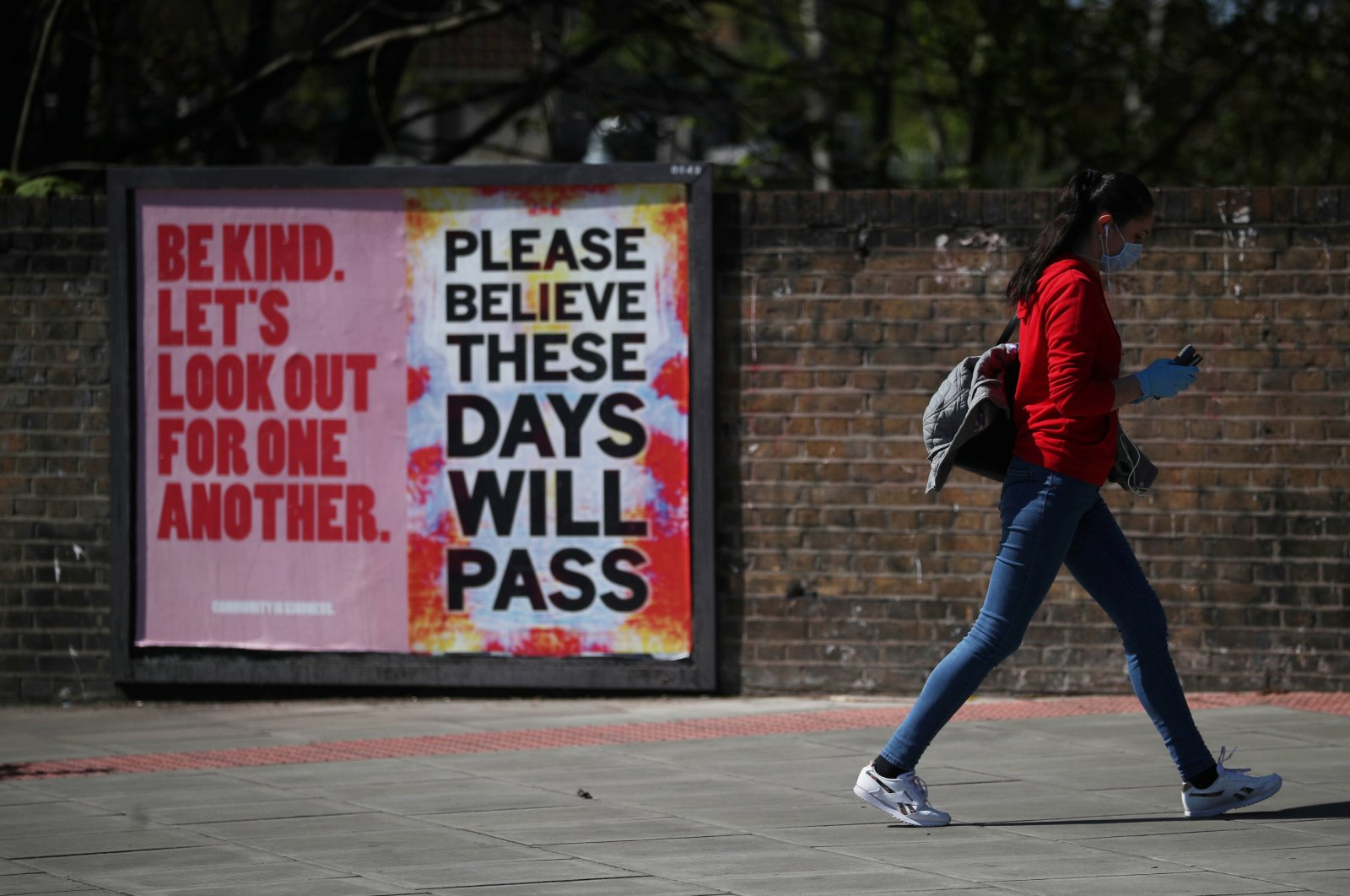 People walk past a poster in Stoke Newington as the spread of the coronavirus disease (COVID-19) continues, London, April 14, 2020. (REUTERS Photo)