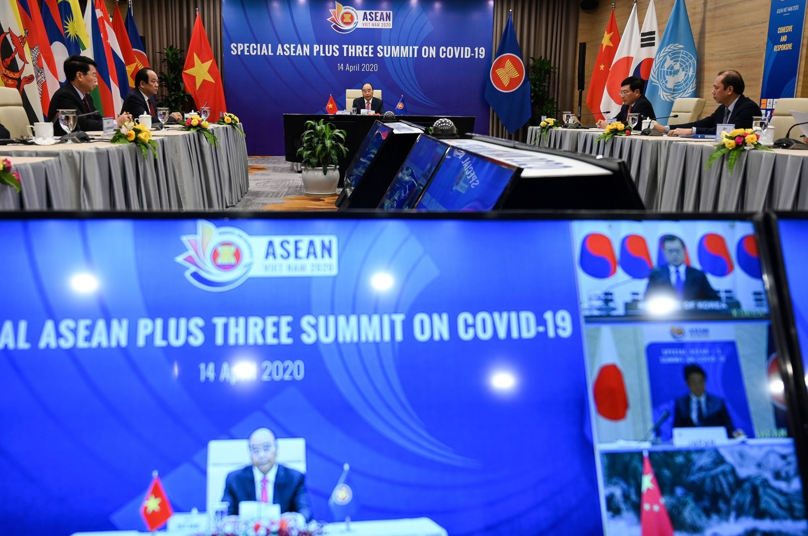 Vietnam's Prime Minister Nguyen Xuan Phuc (C) addresses a live videoconference on the special Association of Southeast Asian Nations (ASEAN) Plus Three Summit on the coronavirus pandemic in Hanoi as South Korea's President Moon Jae-in, Japan's Prime Minister Shinzo Abe and China's Premier Li Keqiang are seen on television screen, April 14, 2020 . (AFP Photo)