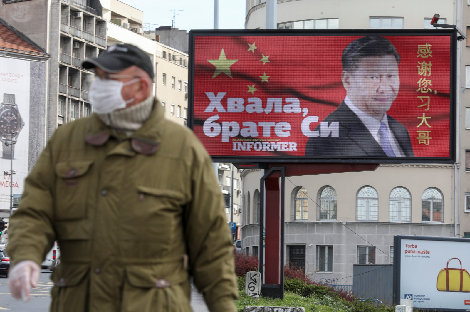 """A man wearing a protective mask passes by a billboard depicting Chinese President Xi Jinping that reads """"Thanks, brother Xi"""" amid COVID-19 pandemic, in Belgrade, Serbia, April 1, 2020. (Reuters Photo)"""