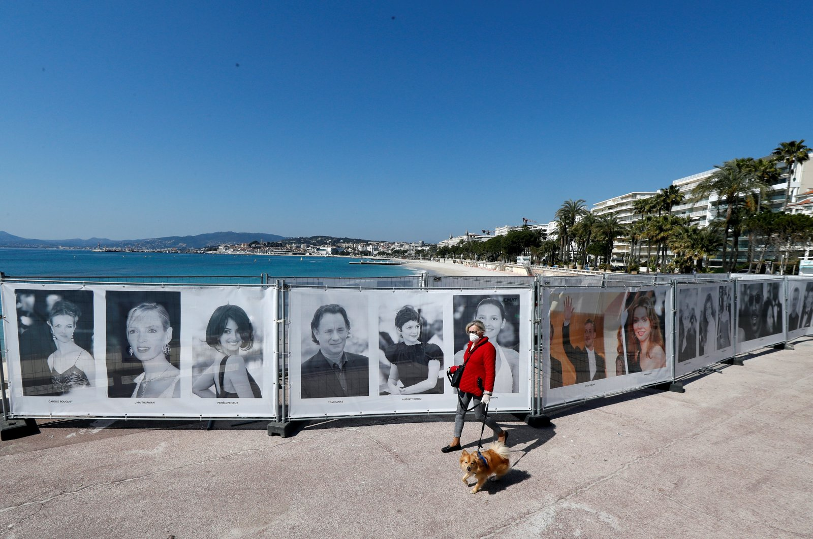 A woman walks past photos of the Cannes Film festival on the Croisette in Cannes as a lockdown is imposed to slow the rate of the coronavirus disease (COVID-19) in France, March 18, 2020. (Reuters Photo)