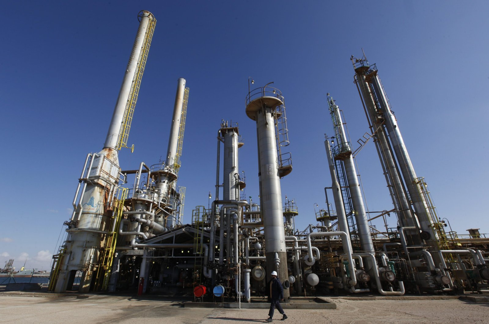 A Libyan oil worker walks in front of a refinery inside the Brega oil complex, in Brega east of Libya, on Saturday, Feb. 26, 2011. (AP Photo)