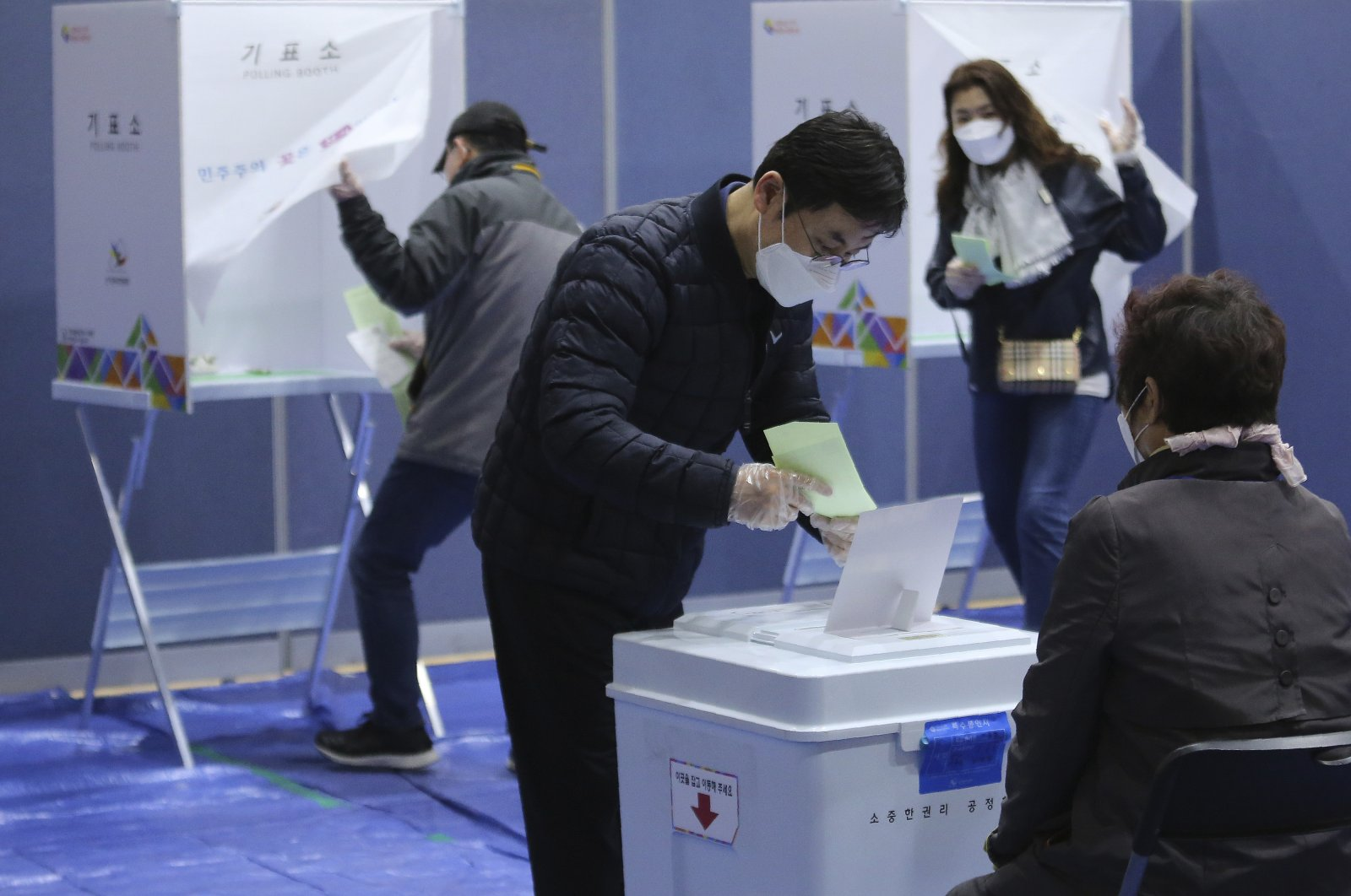 A man wearing a face mask to help protect against the spread of the new coronavirus casts his vote for the parliamentary election at a polling station in Seoul, South Korea, April 15, 2020. (AP Photo)