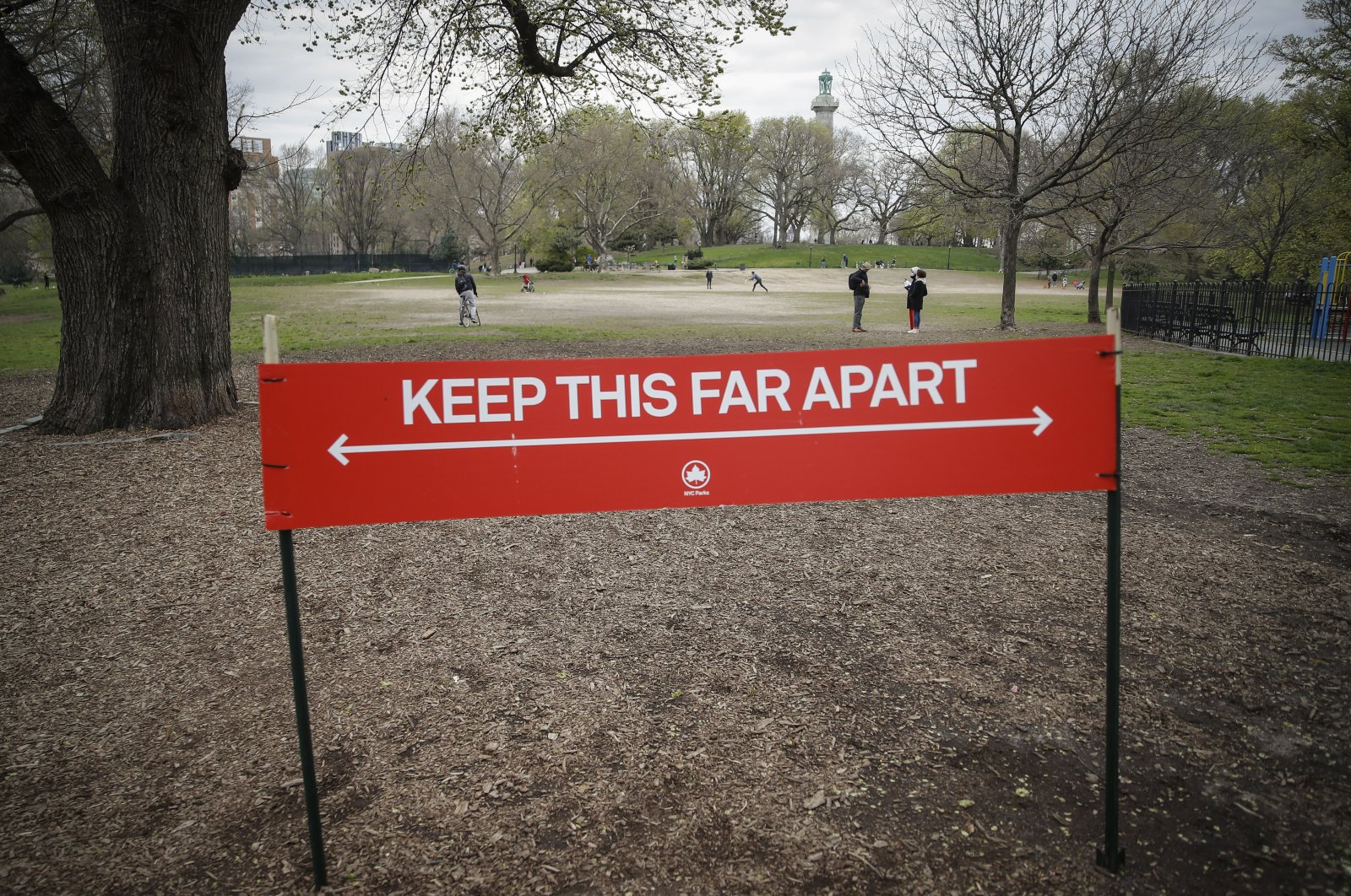A sign by the New York City Department of Parks and Recreation indicates the appropriate measurement for social distancing as pedestrians linger in a field at Fort Greene Park in New York City, New York, U.S., April 14, 2020. (AP Photo)