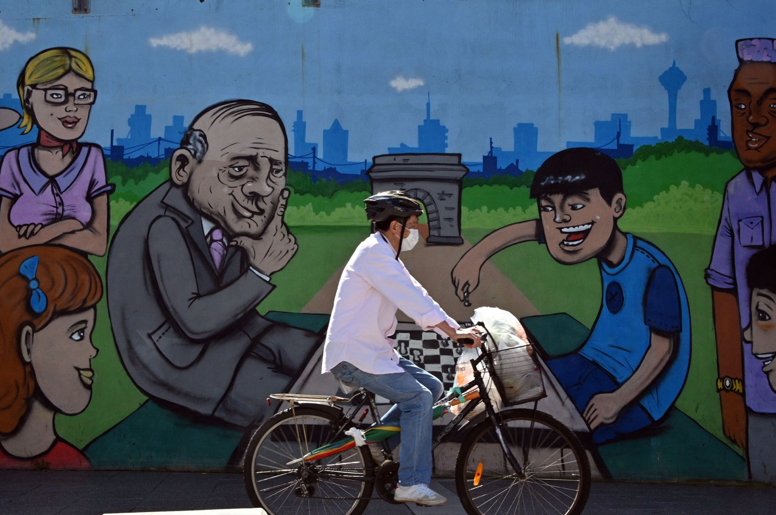 A man wearing a face mask bicycles past a mural in the Burwood suburb of Sydney on April 14, 2020, amid the COVID-19 coronavirus pandemic. (AFP Photo)