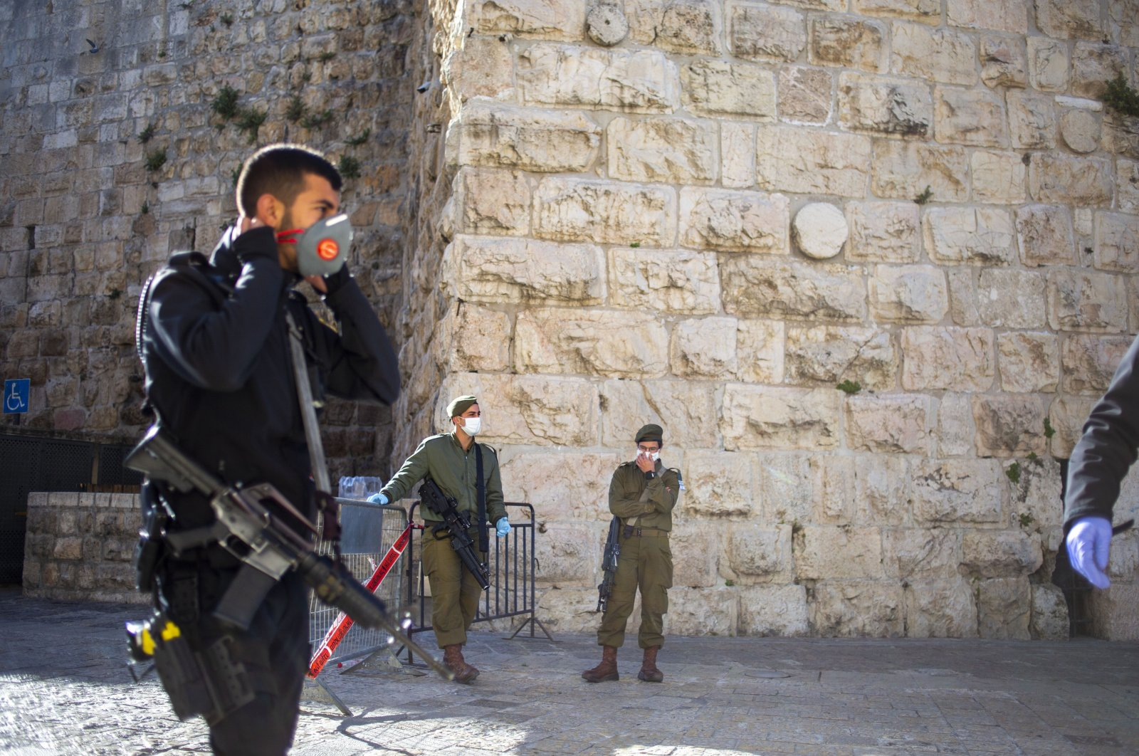 An Israeli police officer and Israeli soldiers block Jaffa gate during a lockdown following government measures in Jerusalem's old city, April 9, 2020. (AP Photo)