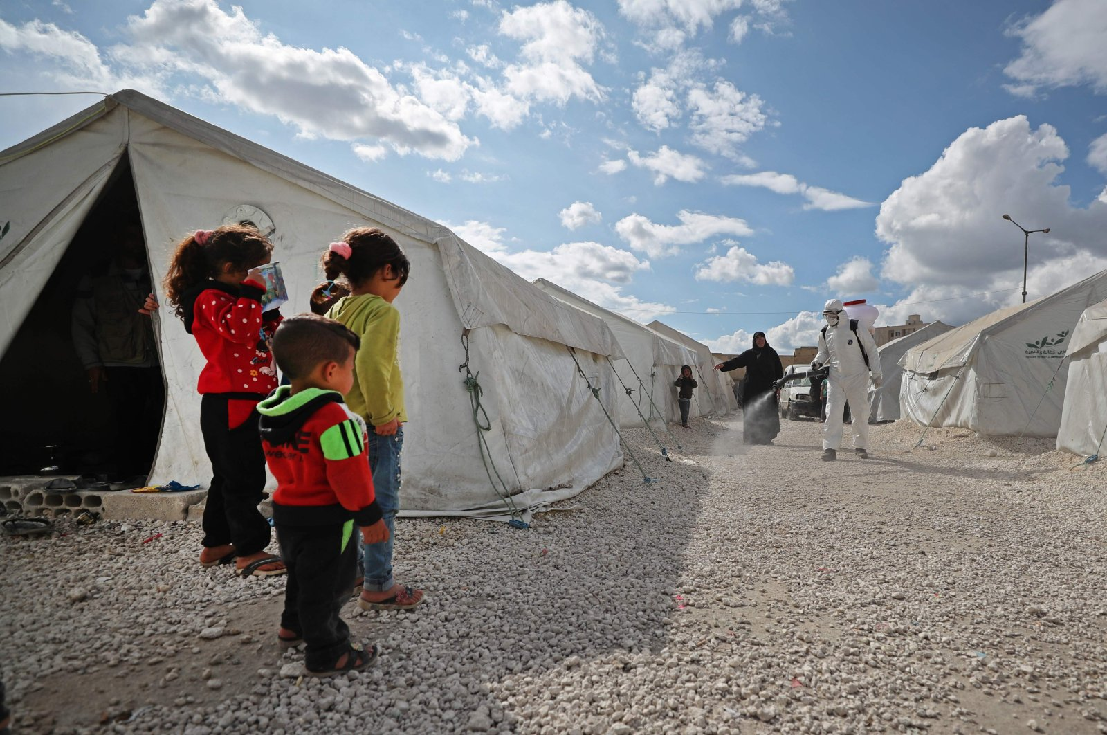Displaced Syrian children watch as a sanitation worker disinfects their camp during a campaign to limit the spread of the coronavirus, Idlib, northwestern Syria, April 9, 2020. (AFP Photo))