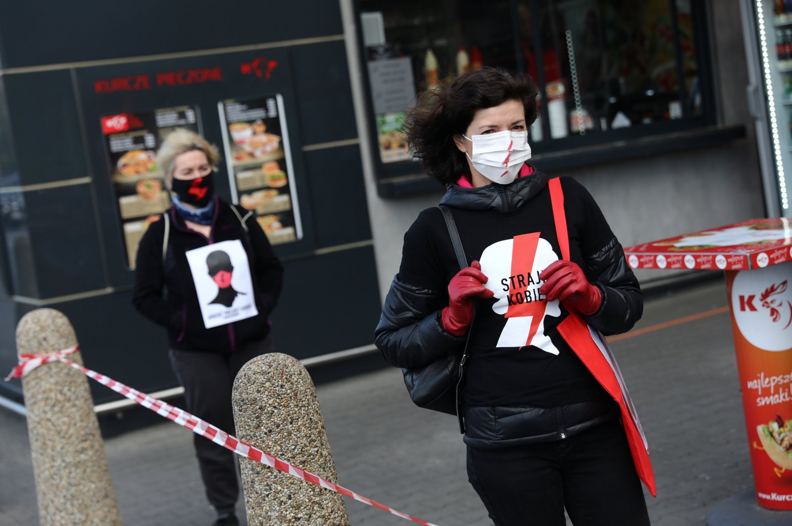 """Women cover their faces and hold """"Women's Strike"""" banners in protest of the Polish parliament's debate on new limits on abortion and sexual education in Krakow, Poland, April 14, 2020.  (Reuters Photo)"""