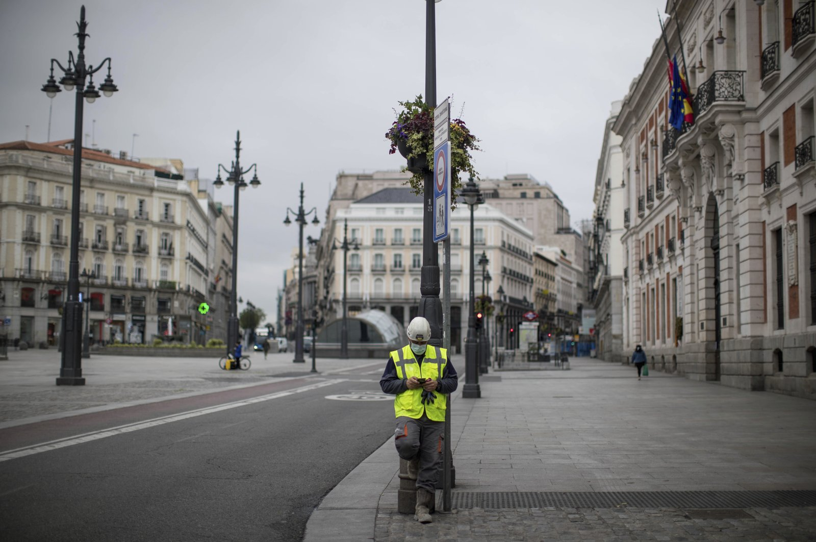 A worker checks his phone at the Sol square in Madrid, Spain, Tuesday, April 14, 2020.  (AP Photo)