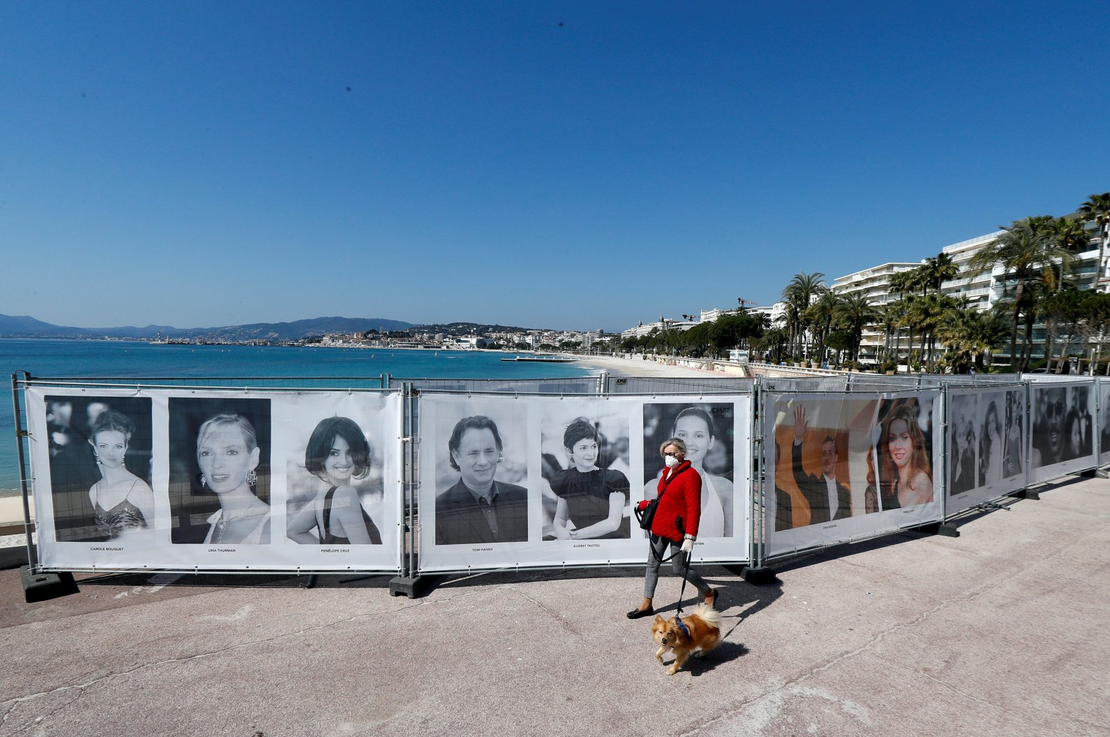 A woman walks past photos of the Cannes Film Festival on the Croisette in Cannes as a lockdown is imposed to slow the rate of the coronavirus in France, March 18, 2020. (Reuters Photo)