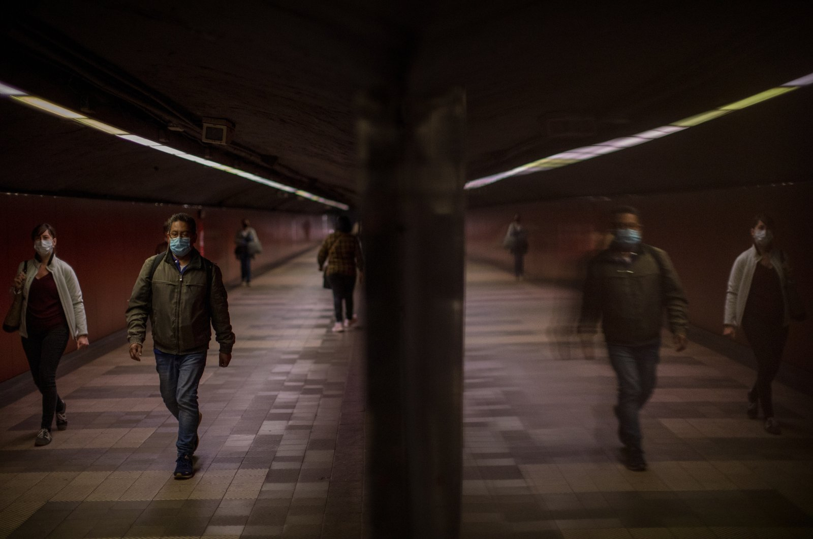 Passengers wearing face masks to prevent the spread of the coronavirus walk along a tunnel connecting platforms in a metro station, Barcelona, Spain, April 15, 2020. (AP Photo)