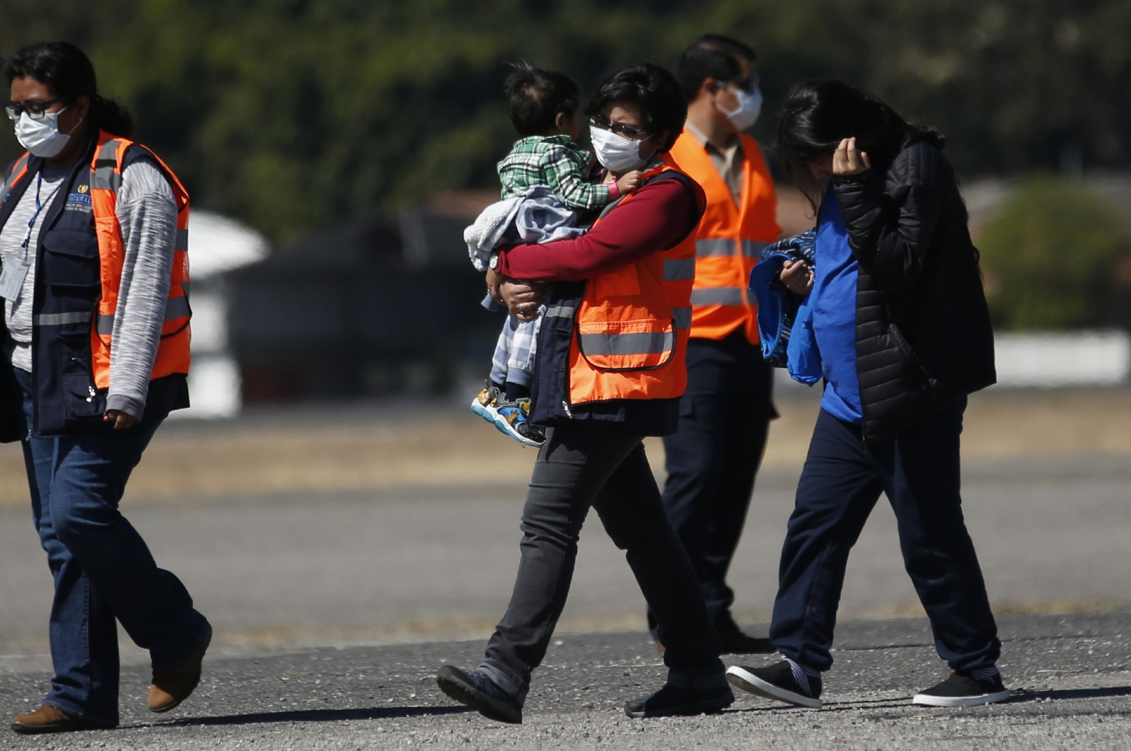 An immigration worker, wearing an orange jacket and a mask as a precaution against the coronavirus, carries a young Guatemalan migrant who was deported from the U.S., followed by another deportee, at La Aurora International Airport, Guatemala City, March 12, 2020. (AP Photo)