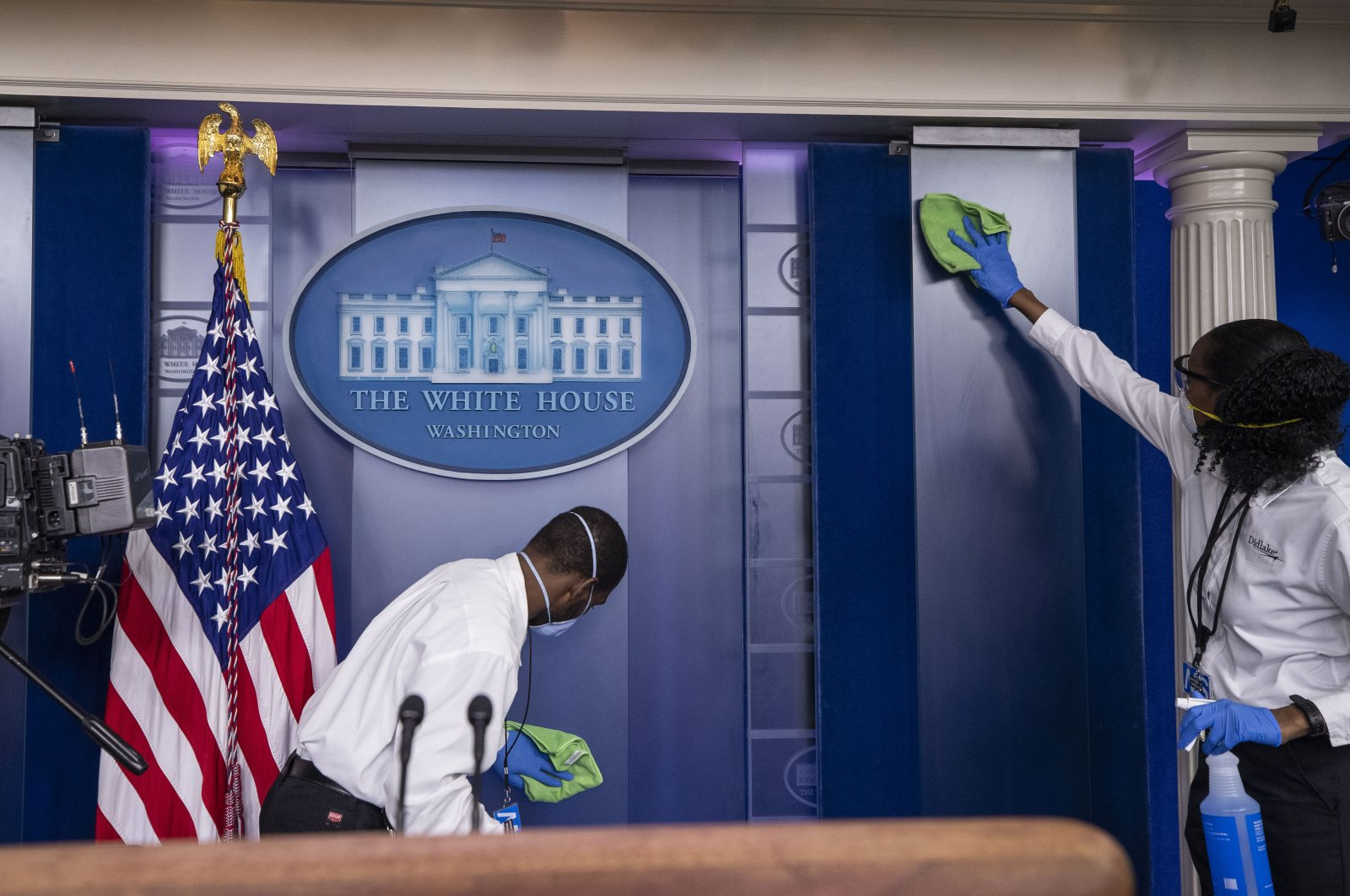 A cleaning crew wipes down surfaces before U.S. President Donald Trump speaks about the coronavirus in the James Brady Press Briefing Room at the White House, Washington, April 13, 2020. (AP Photo)