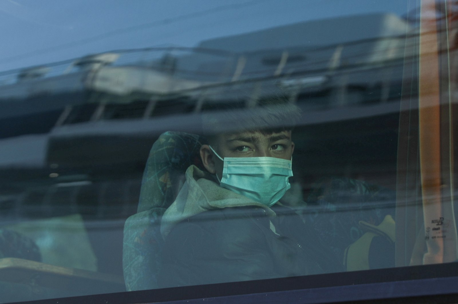 An unaccompanied child from an overcrowded migrant camp who will be transferred to either Germany or Luxembourg wears a protective face mask as a precaution against the spread of coronavirus disease (COVID-19) as he boards a bus at the port of Piraeus, Greece, April 15, 2020. (Reuters Photo)