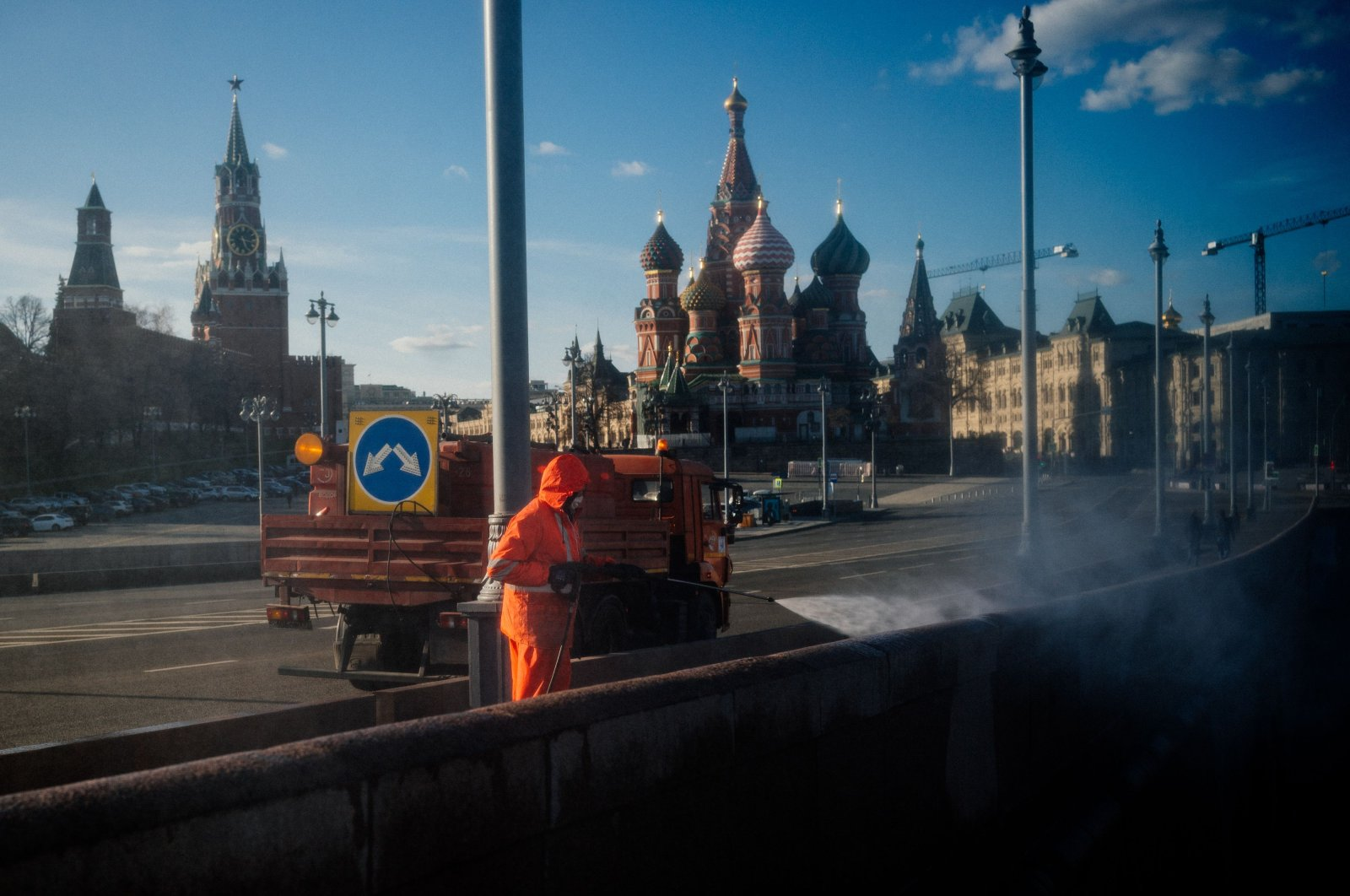 A municipal worker cleans and disinfects a bridge near the Kremlin in downtown Moscow on April 12, 2020, during a strict lockdown in Russia to stop the spread of the novel coronavirus COVID-19. (AFP Photo)