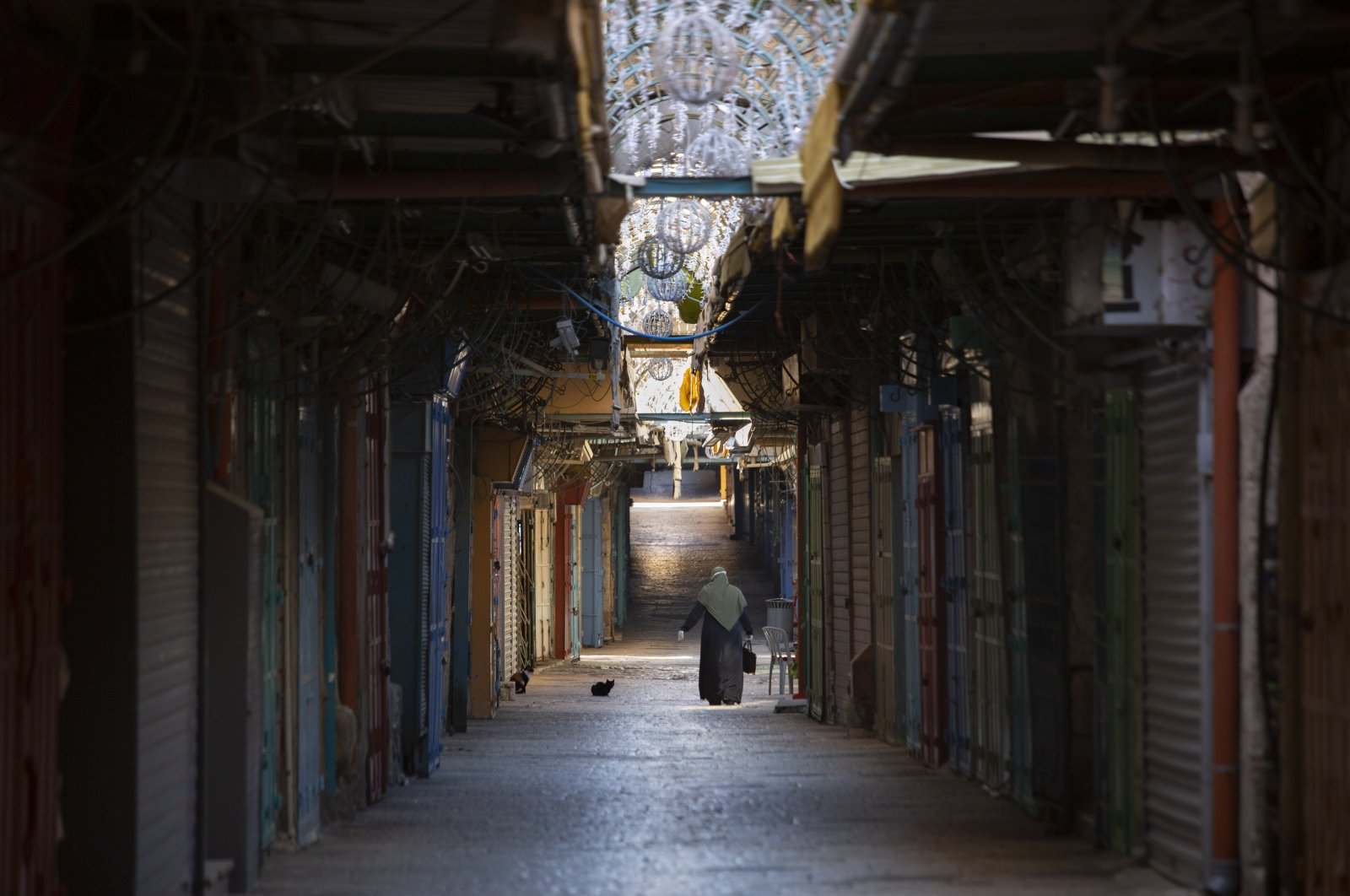 A woman walks down an alley in a closed market during government measures to stop the spread of the coronavirus in Jerusalem's Old City, April 13, 2020. (AP Photo)