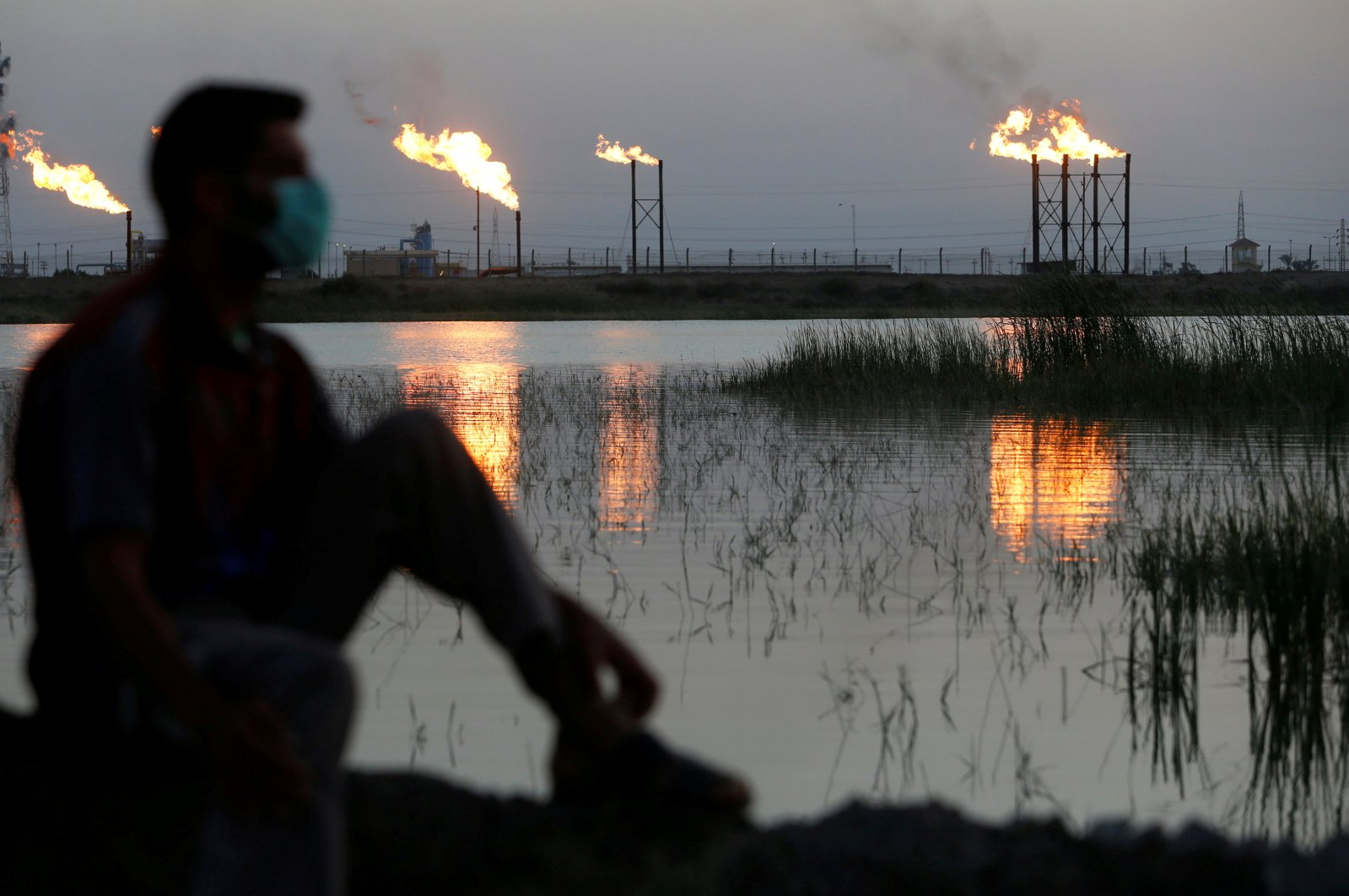 Flames emerge from flare stacks at Nahr Bin Umar oil field, as a man is seen wearing a protective face mask following the outbreak of the coronavirus, north of Basra, Iraq, March 9, 2020. (Reuters Photo)