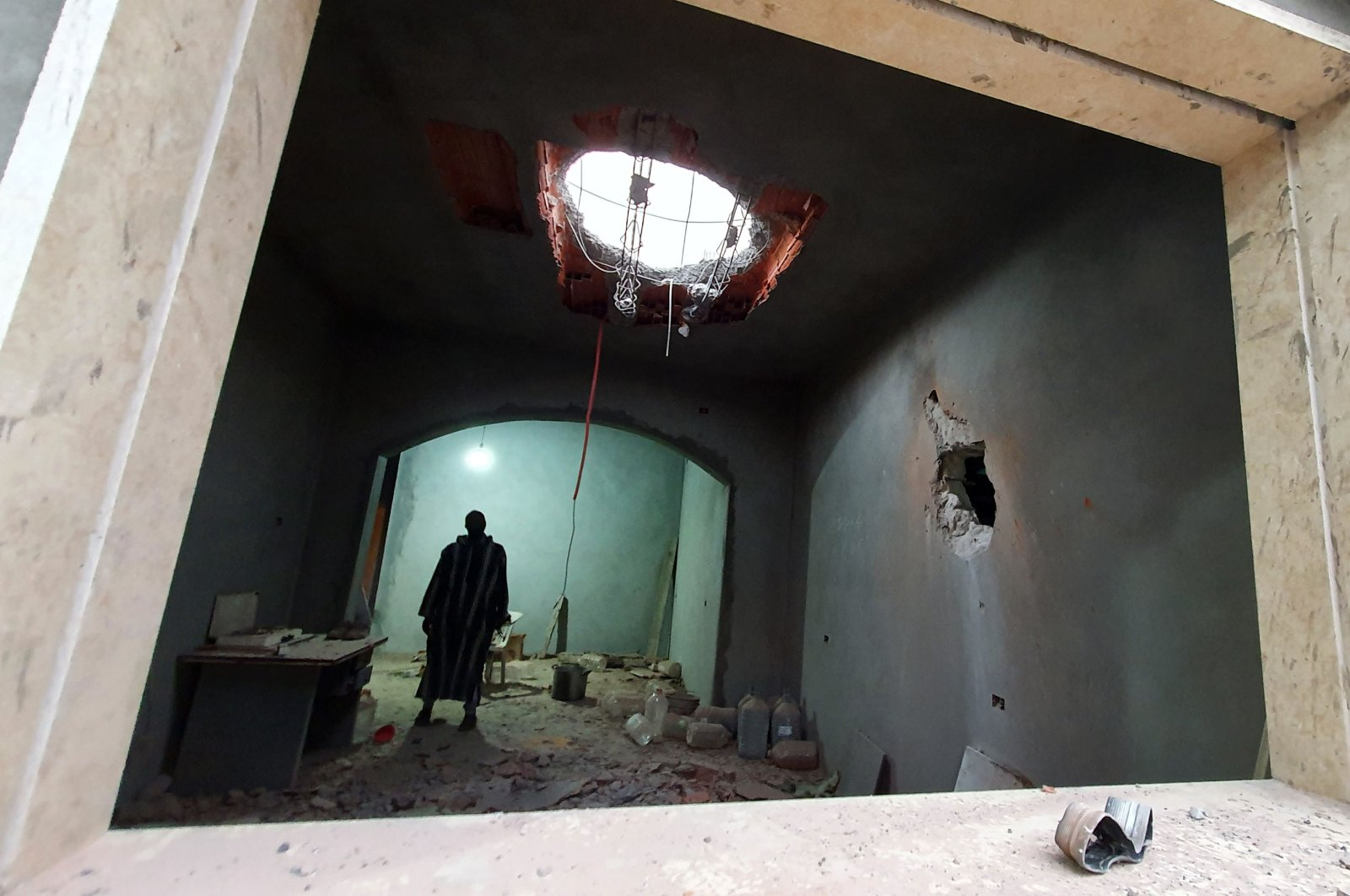 A Libyan man stands at the site of shelling on the residential area of Arada in the capital Tripoli, Tuesday, April 14, 2020. (AFP)