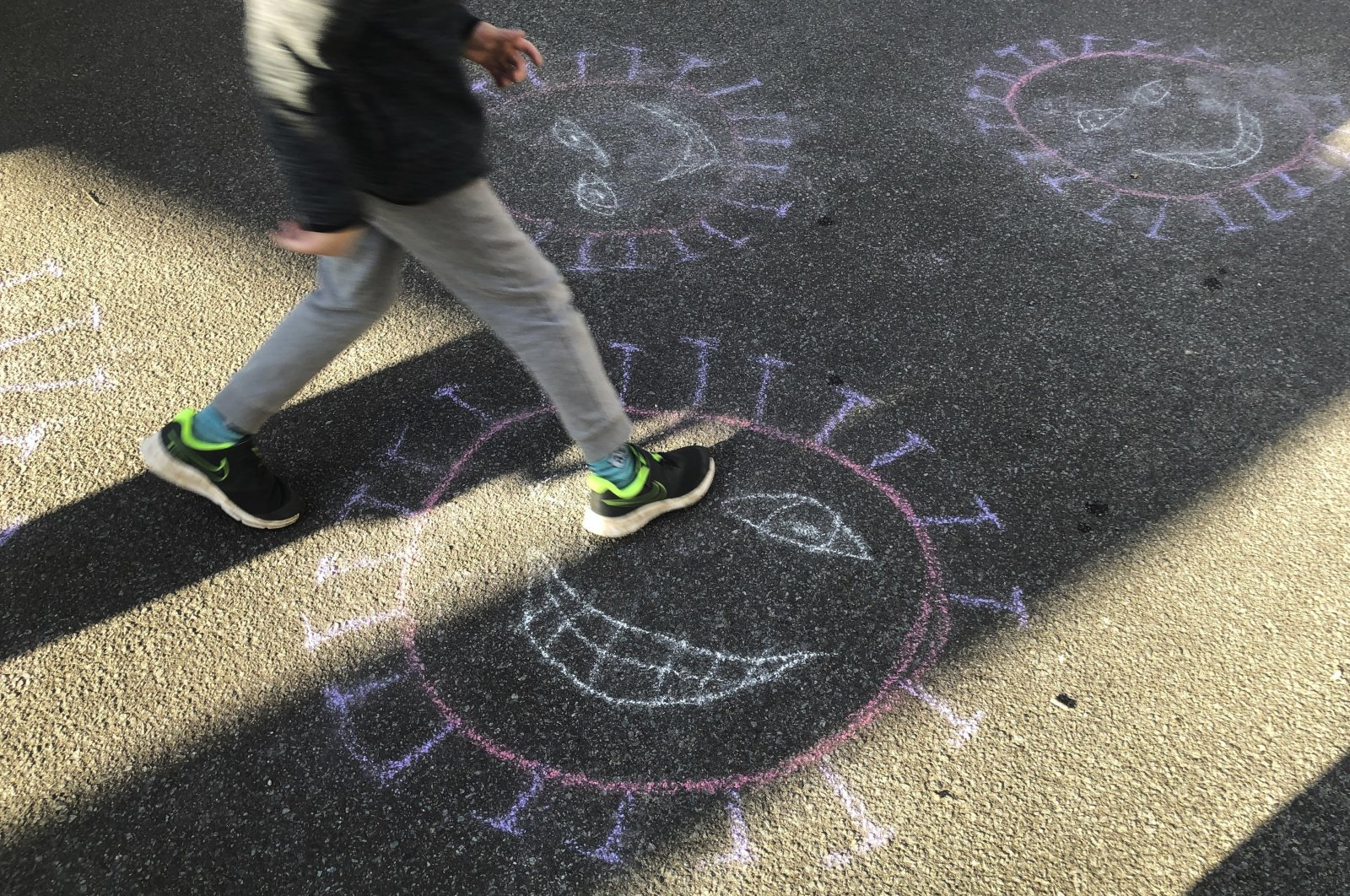 An artistic crayon depiction of the coronavirus painted by children on a street in Berlin, Germany, April 14, 2020. (AP Photo)