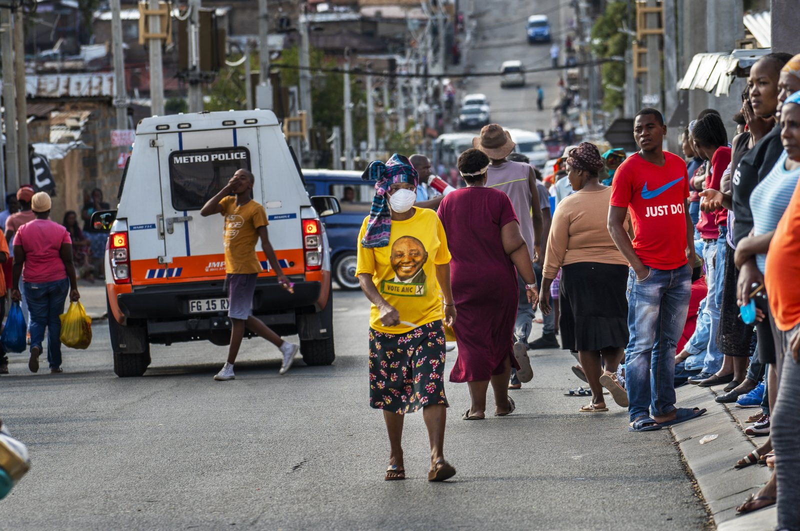 A woman wearing a mask and an African National Congress shirt with the face of South African President Cyril Ramaphosa walks in the Alexandra township of Johannesburg Wednesday, April 15, 2020. (AP)