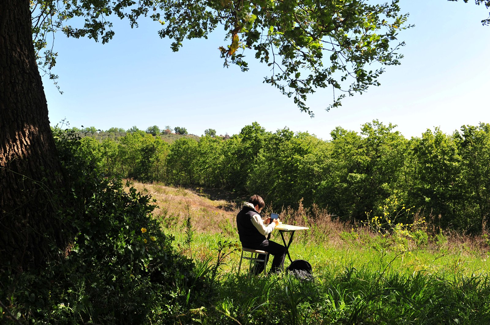 Giulio Giovannini, 12, with a tablet, a small camping table and a chair, studies on the top of a hill where he is able to access the internet so that he can participate in online lessons while the schools remain closed due lockdown, in Scansano, Italy, April 15, 2020. (Reuters Photo)