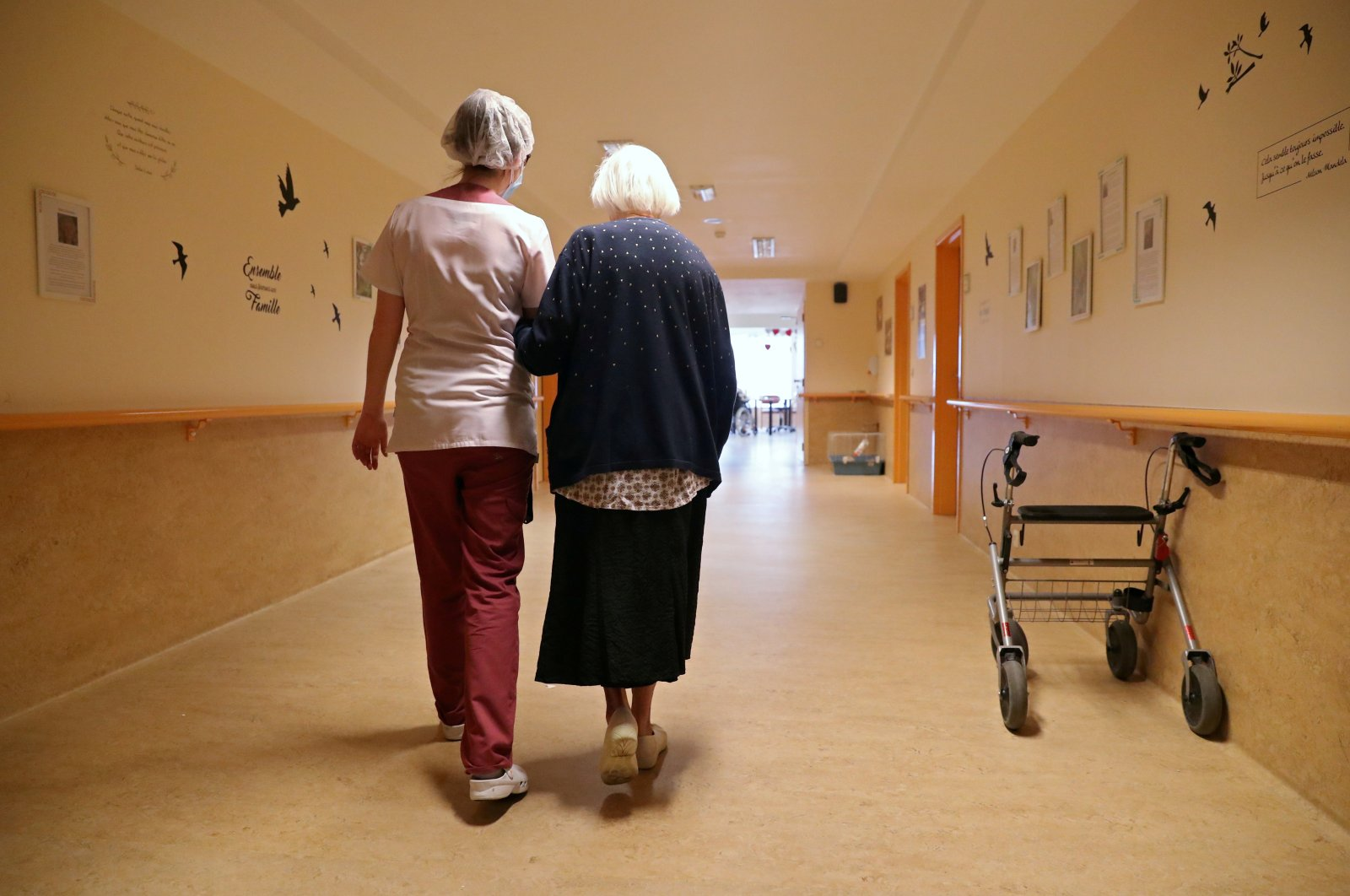 An occupational therapist walks with a woman of the elderly residence Christalain, Brussels, April 14, 2020. (REUTERS Photo)