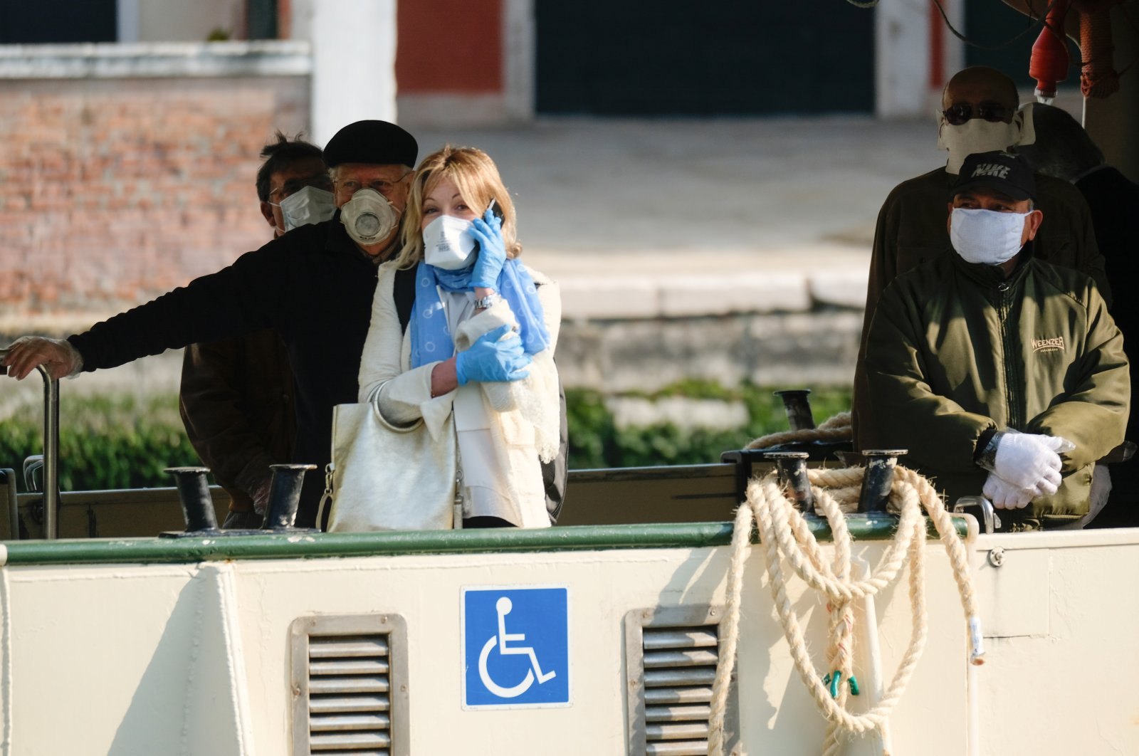 People wearing protective masks and gloves are seen on a water bus as the Italian government allows the reopening of some shops while a nationwide lockdown continues, Venice, April 14, 2020. (REUTERS Photo)