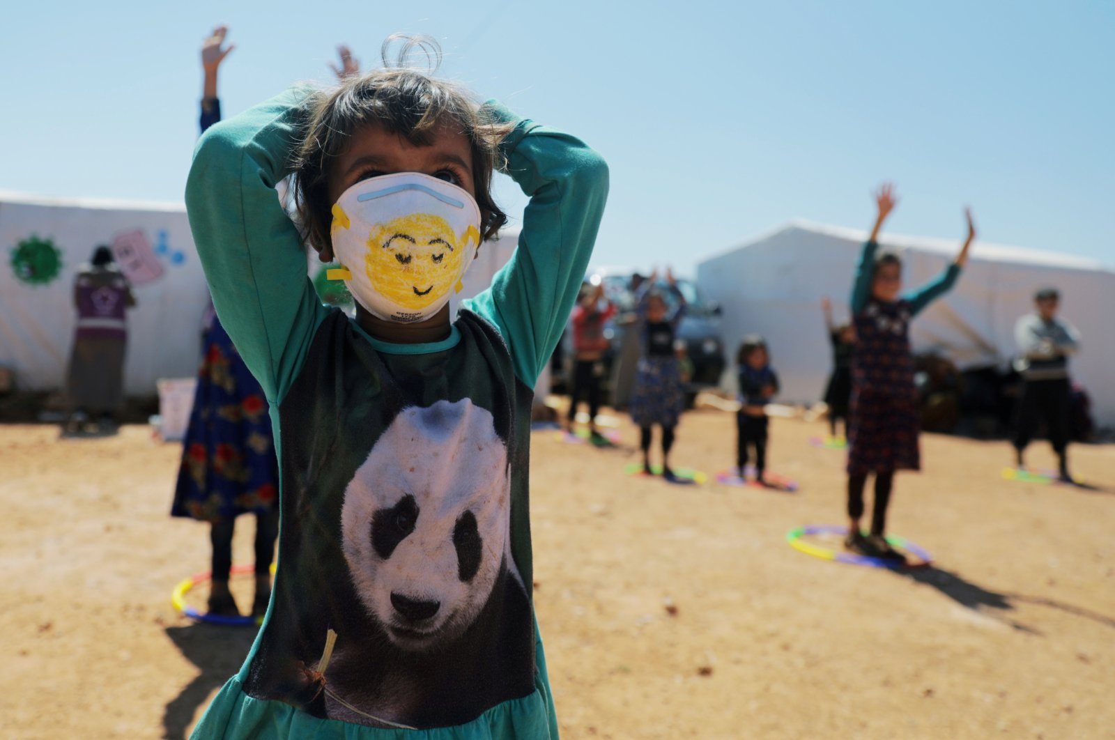 A displaced girl wears a face mask as she takes part in an event organzied by Violet Organization, in an effort to spread awareness and encourage safety amid coronavirus disease (COVID-19) fears, at a camp in the town of Maarat Masrin in northern Idlib, Syria, Tuesday, April 14, 2020. (REUTERS)