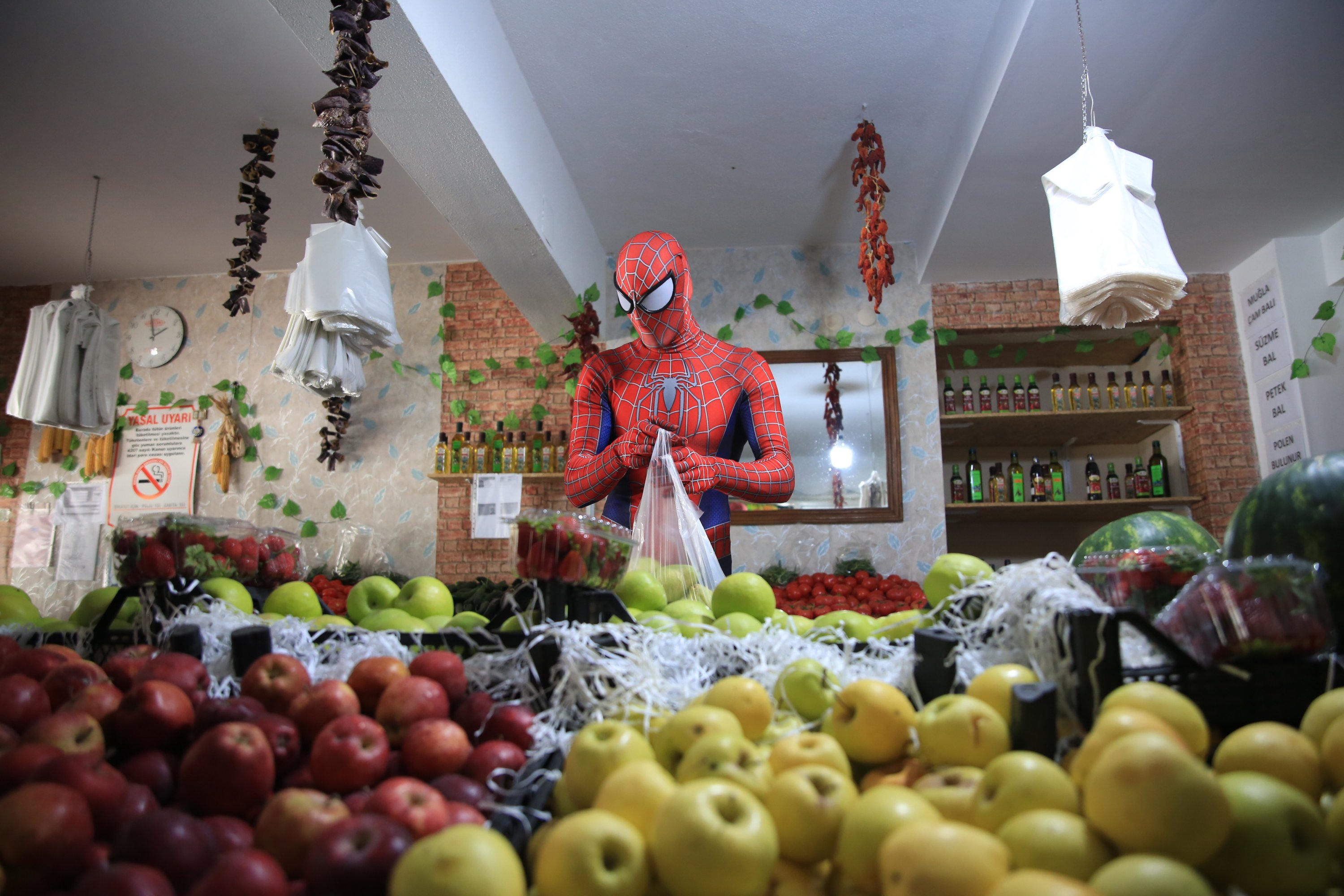 Burak Soylu, wearing the Spiderman costume, picks groceries for citizens, who are staying at home due the coronavirus (COVID-19) pandemic in Antalya, Turkey, Tuesday, April 14, 2020. (AA Photo)