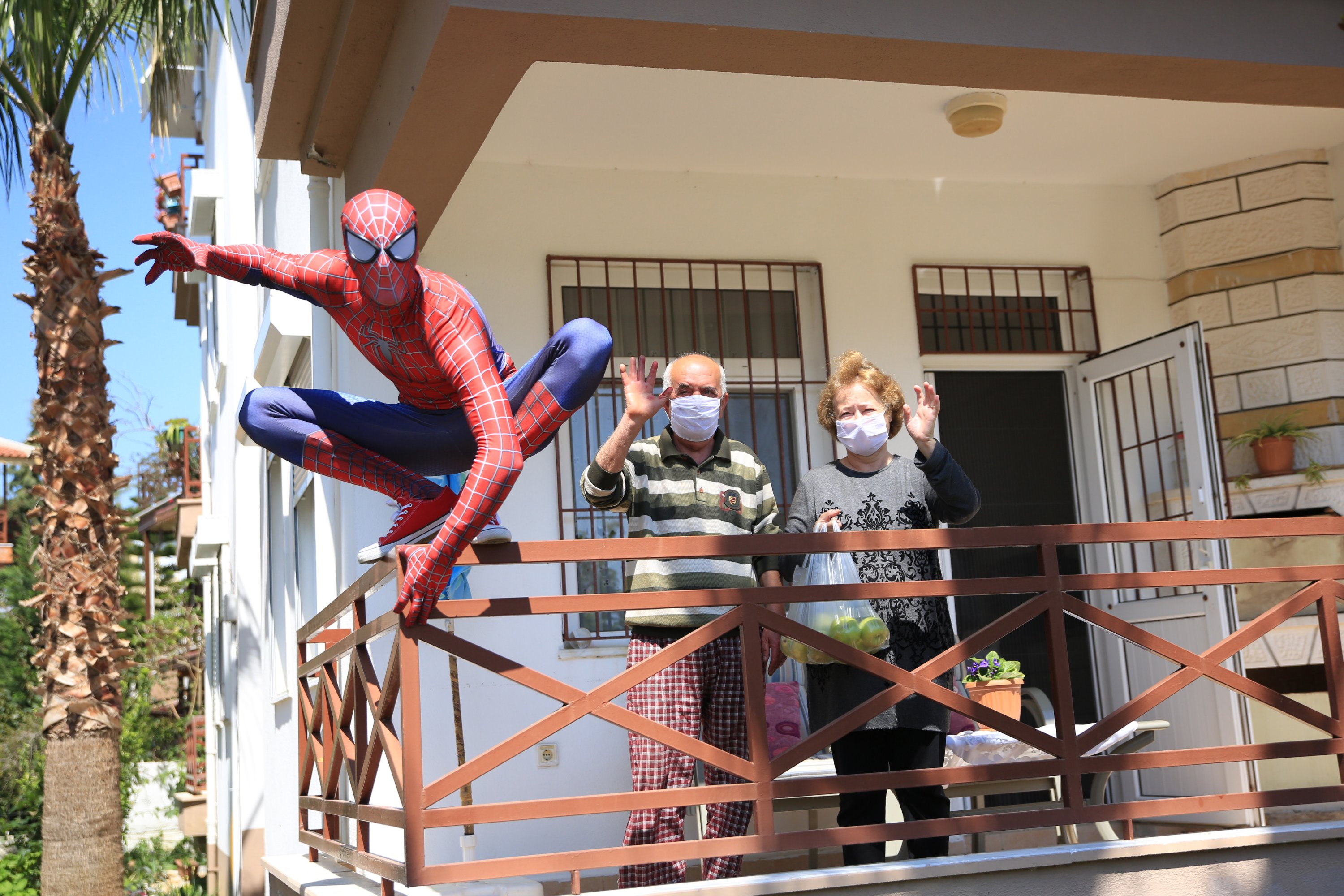 Burak Soylu, wearing the Spiderman costume, poses for a photo on a balcony fence after bringing groceries for a couple, who are staying at home due the coronavirus (COVID-19) pandemic in Antalya, Turkey, Tuesday, April 14, 2020. (AA Photo)