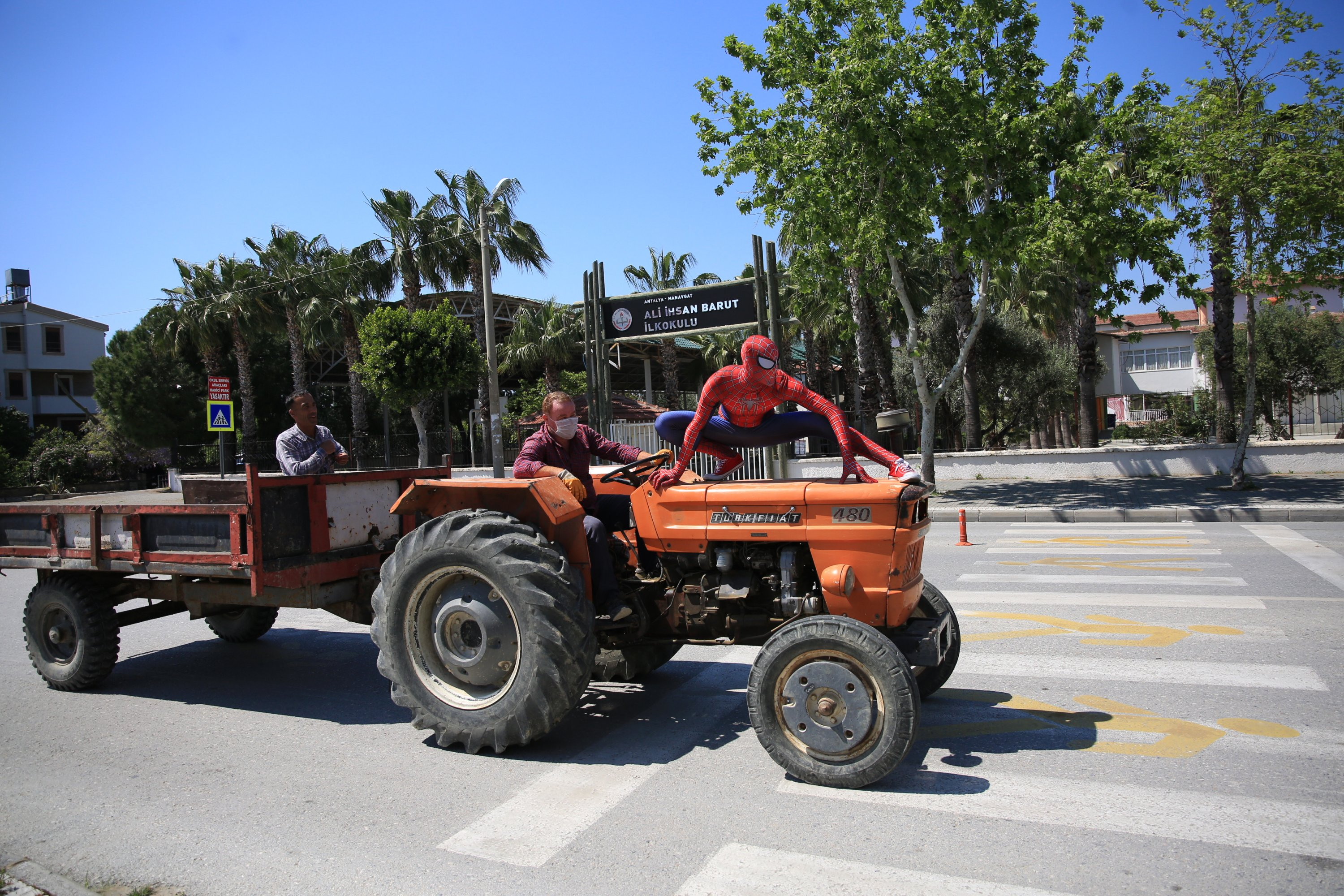 Burak Soylu, wearing the Spiderman costume, poses for a photo on top of a tractor in Antalya, Turkey, Tuesday, April 14, 2020. (AA Photo)