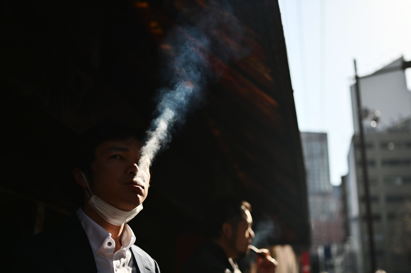 People smoke in a designated smoking area on a street in the Yurakucho area, Tokyo, Japan, March 26, 2020. (AFP Photo)