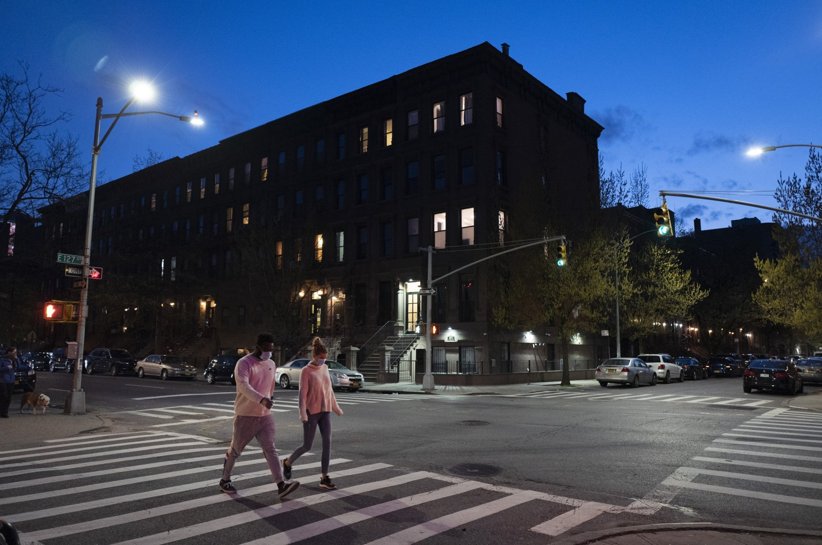 People wearing masks cross the street at Langston Hughes Place in Harlem during the coronavirus pandemic, in New York City, New York, U.S., April 15, 2020. (AP Photo)