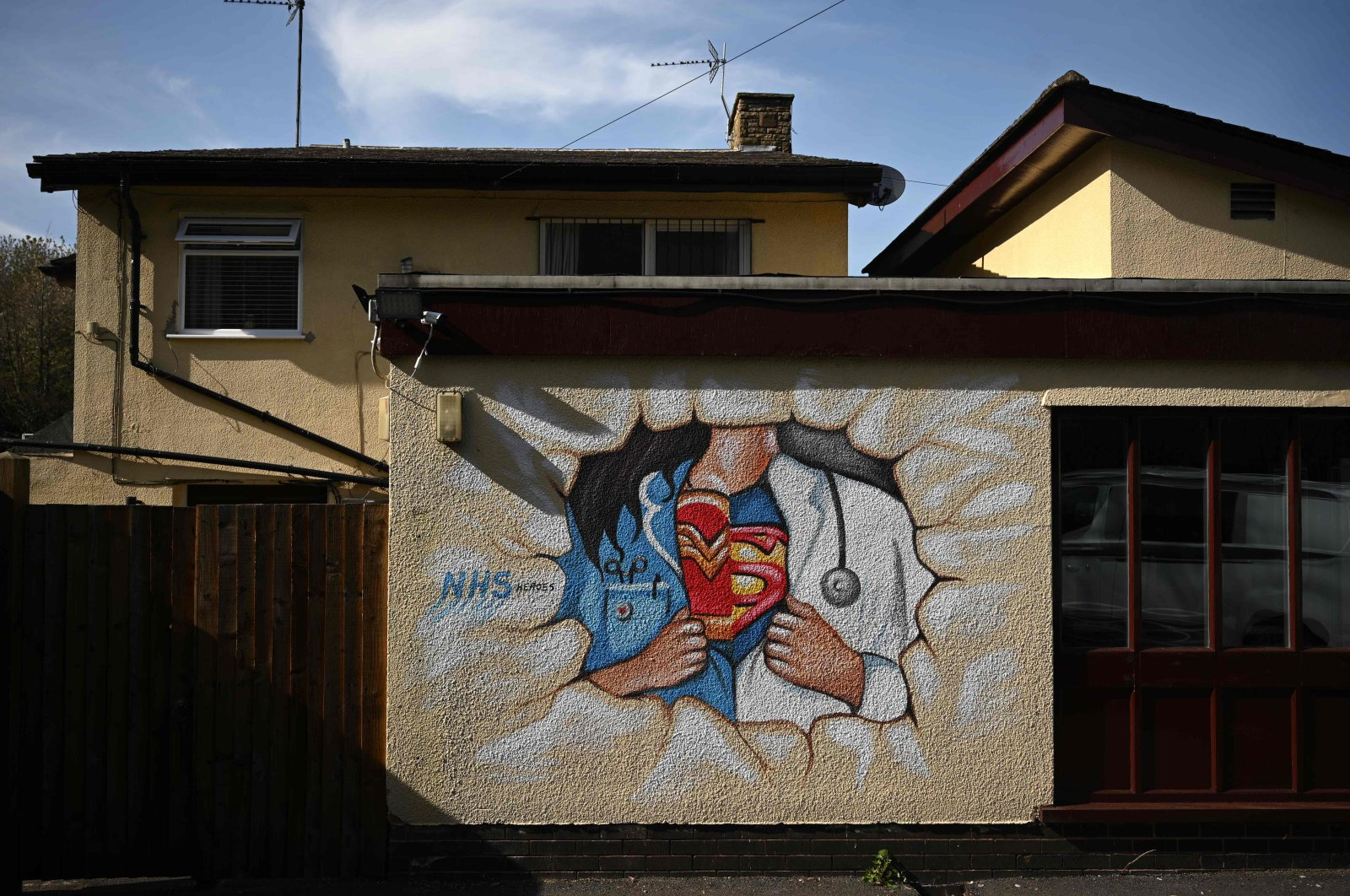 Graffiti depicts the badge of a superhero concealed under a nurse's and doctor's uniform in homage to the efforts of NHS staff during the coronavirus crisis on a wall in Pontefract, northern England, April 14, 2020. (AFP Photo)