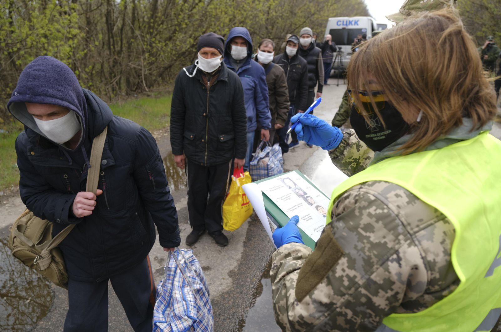 Russia-backed separatists war prisoners wearing masks to protect against coronavirus walk during a prisoner exchange, near Gorlivka, Donetsk region, eastern Ukraine, April 16, 2020. (AP Photo)