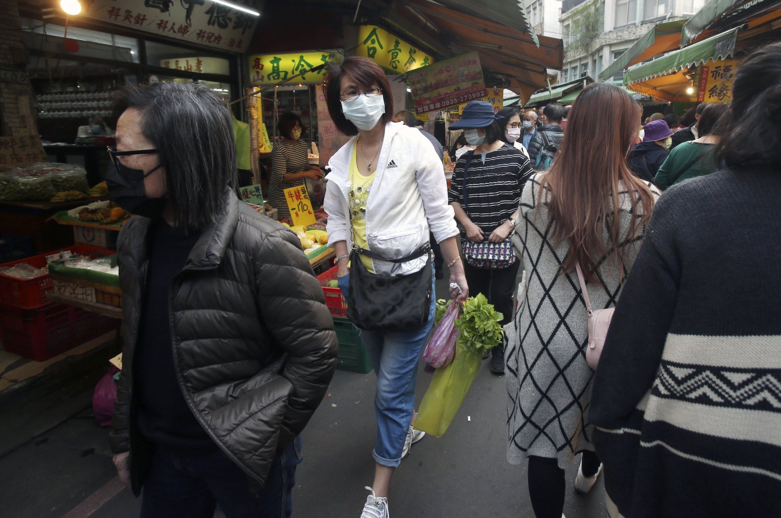 People wear face masks to help curb the spread of the coronavirus as they shop at a market in Taipei, Taiwan, Tuesday, April 14, 2020. (AP Photo)