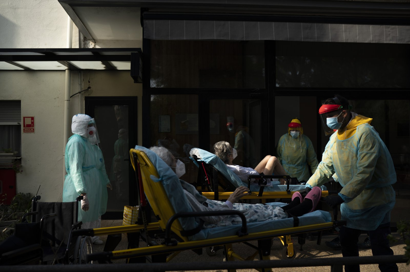 Health workers transport two elderly residents of a nursing home on stretchers who tested positive for the coronavirus in Barcelona, Spain, April 11, 2020. (AP Photo)