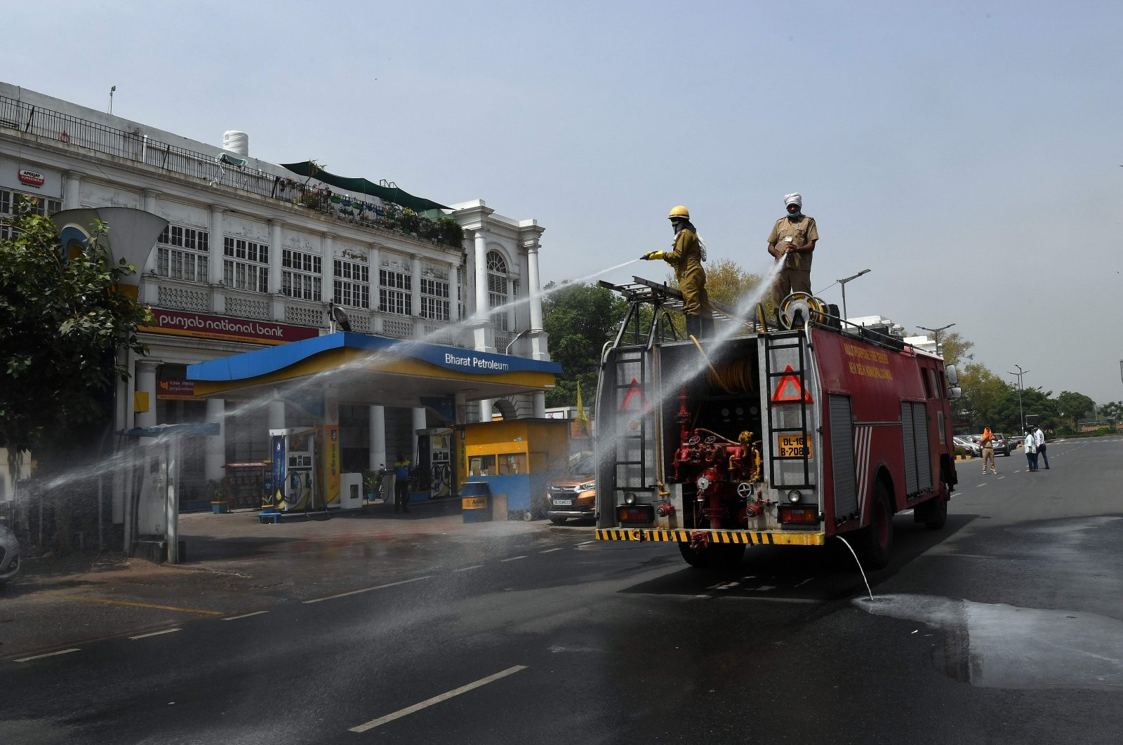 Delhi Fire Service (DFS) personnel spray disinfectant chemicals along a road during a government-imposed nationwide lockdown as a preventive measure against the COVID-19 coronavirus in New Delhi on April 16, 2020. (AFP Photo)