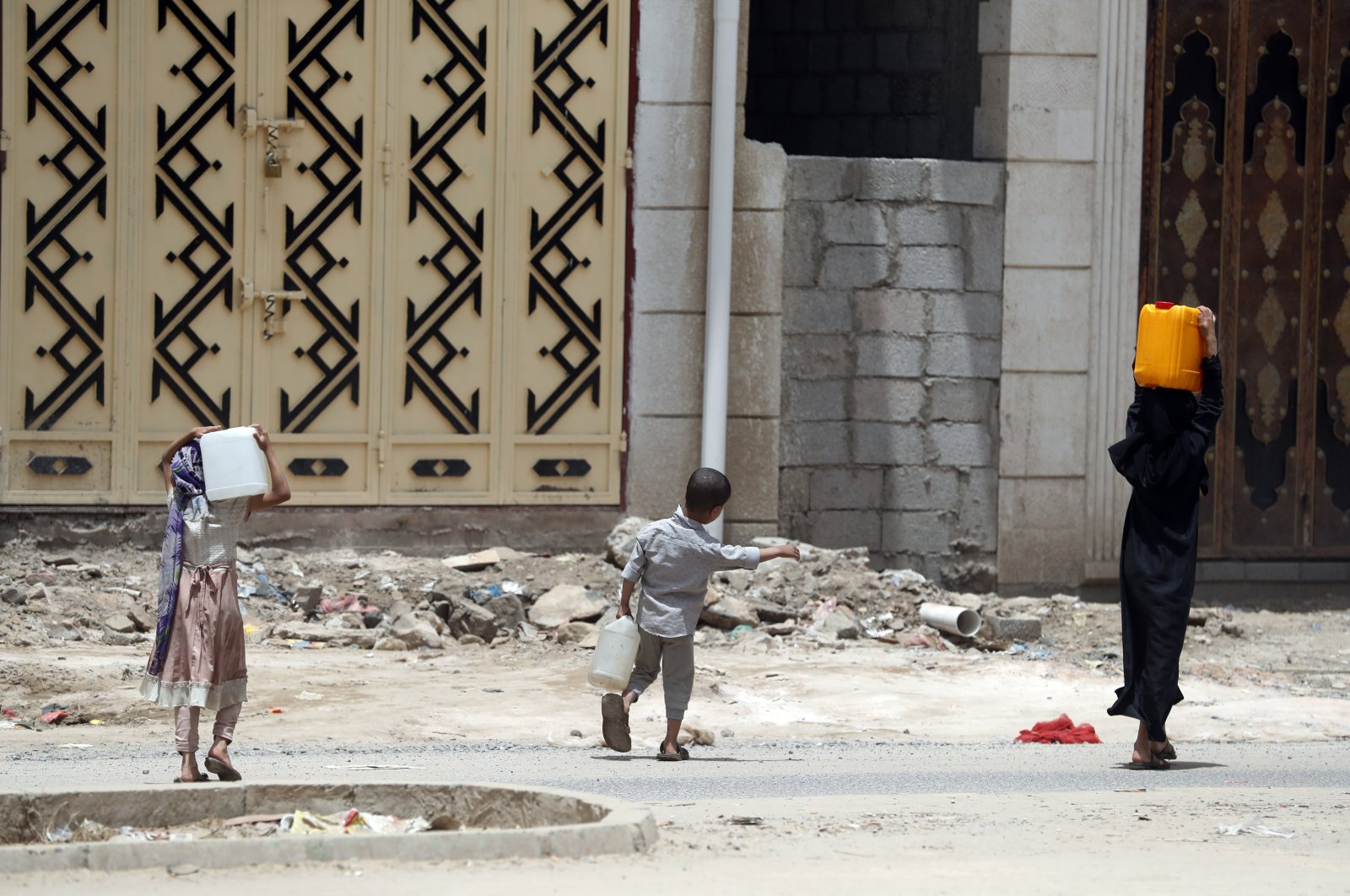 Yemeni children carry water-full bottles after filling them from a charity tap amid concerns over the spread of the coronavirus COVID-19, in Sanaa, Yemen, April 5, 2020. (EPA Photo)