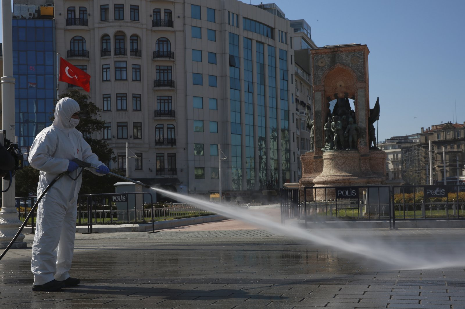 Workers clean and disinfect surfaces in the city's iconic Taksim Square amid the coronavirus outbreak, Istanbul, Turkey, April 12, 2020. (AP Photo)