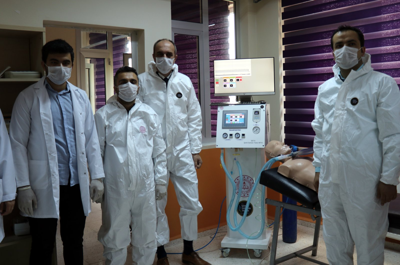 Staff and students of Şehit Serkan Talan Vocational and Technical High School pose with a ventilator device, Hatay, Turkey, April 16, 2020. (AA Photo)
