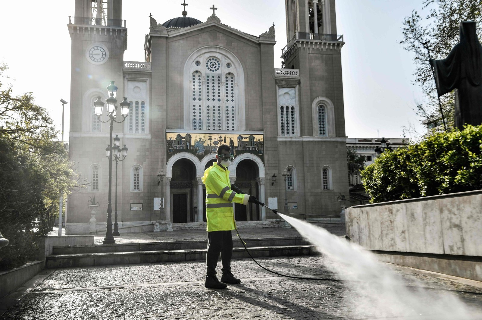 A municipal worker disinfects the forecourt outside Athens Metropolitan Church, Athens, Greece, April 15, 2020. (AFP Photo)