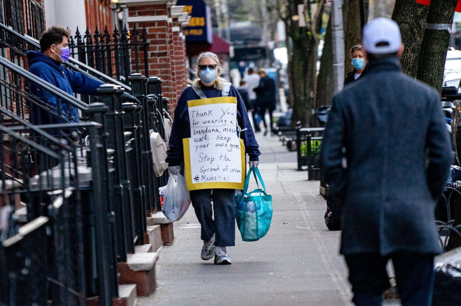 A person walks down a street with a sign thanking people for wearing face coverage on April 15, 2020, in New York City. (AFP Photo)