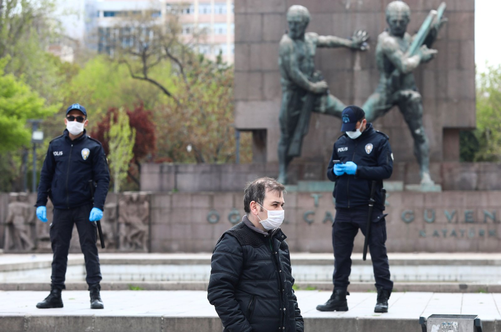 A man wearing a protective facemask walks past two police officers in Ankara, Thursday, April 16, 2020. (AFP Photo)