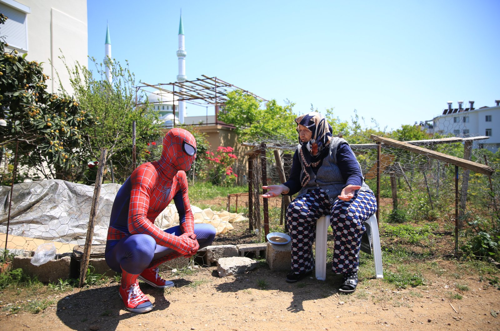 Burak Soylu in his Spider-Man costume (L) chats with a local, Antalya, Turkey, Tuesday, April 14, 2020. (AA Photo)