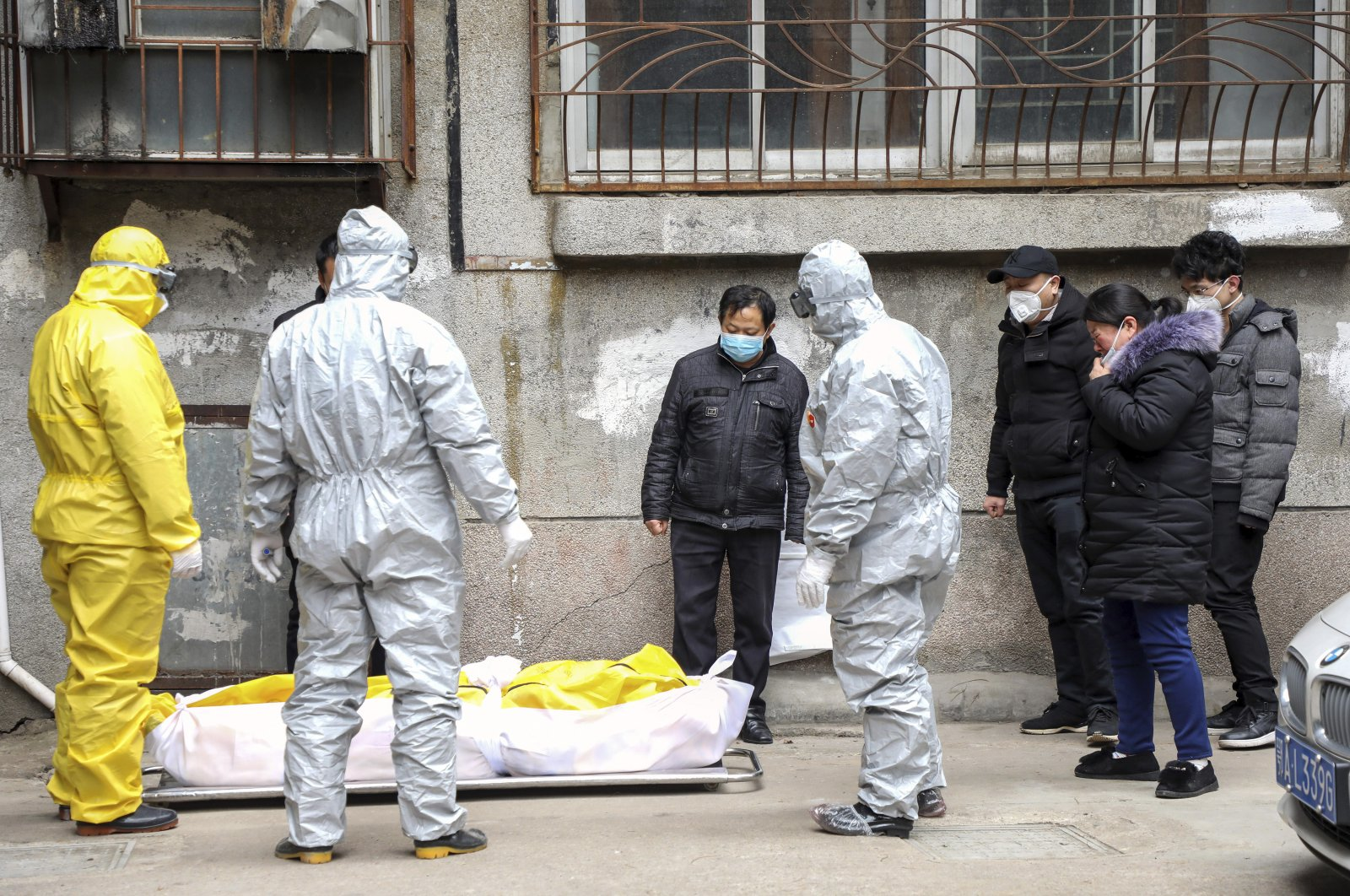 Funeral home workers remove the body of a person suspected to have died during the coronavirus outbreak from a residential building in Wuhan in central China's Hubei Province, Feb. 1, 2020. (Chinatopix via AP)