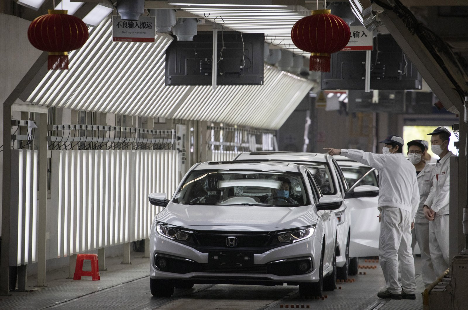 Workers wearing masks against the coronavirus chat near finished cars rolled out at the Dongfeng Honda Automobile Co., Ltd. factory in Wuhan in central China's Hubei province, April 8, 2020. (AP Photo)