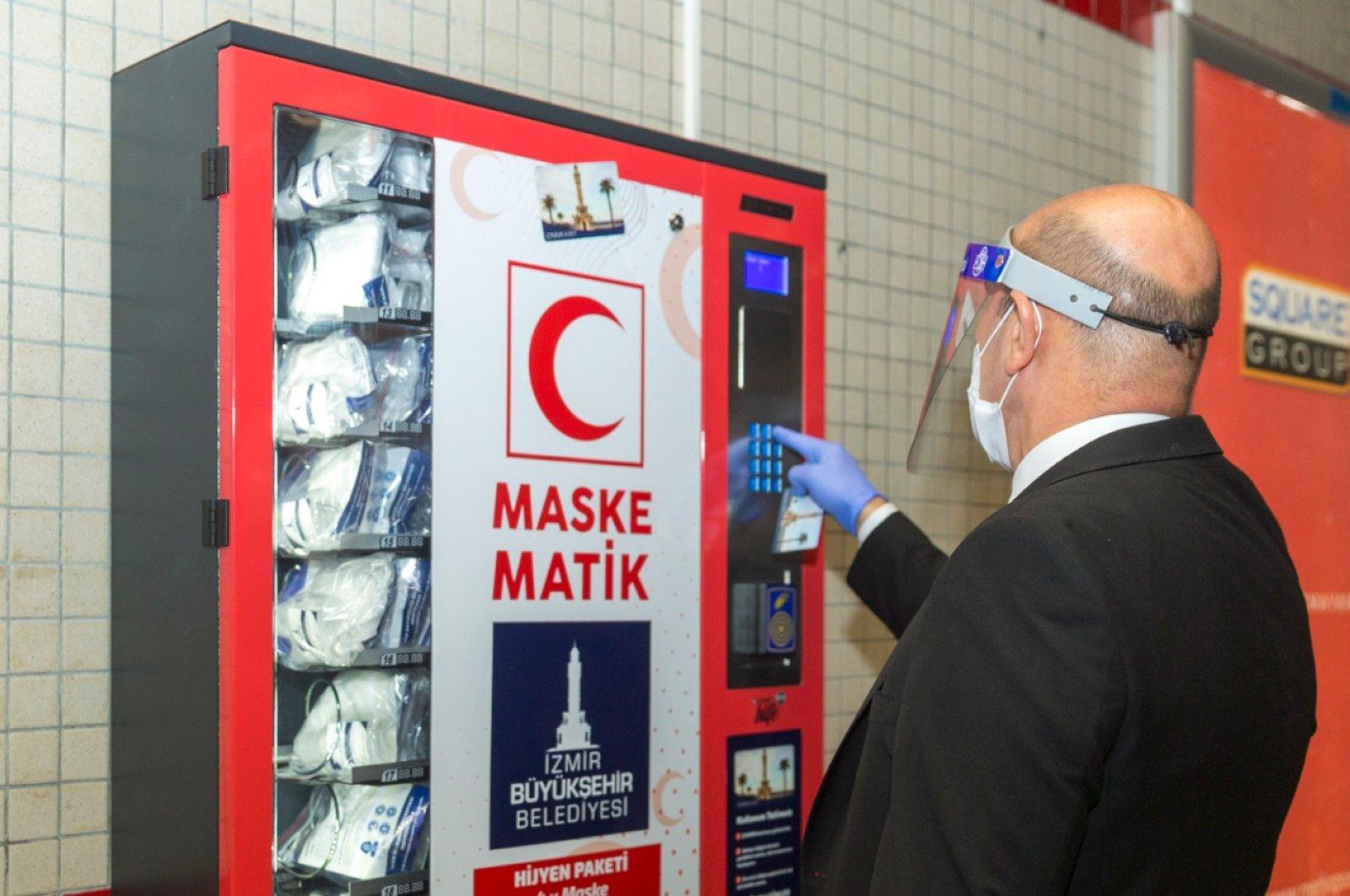 A man uses a mask vending machine in Konak metro station, İzmir, Turkey, April 17, 2020. (AA Photo)