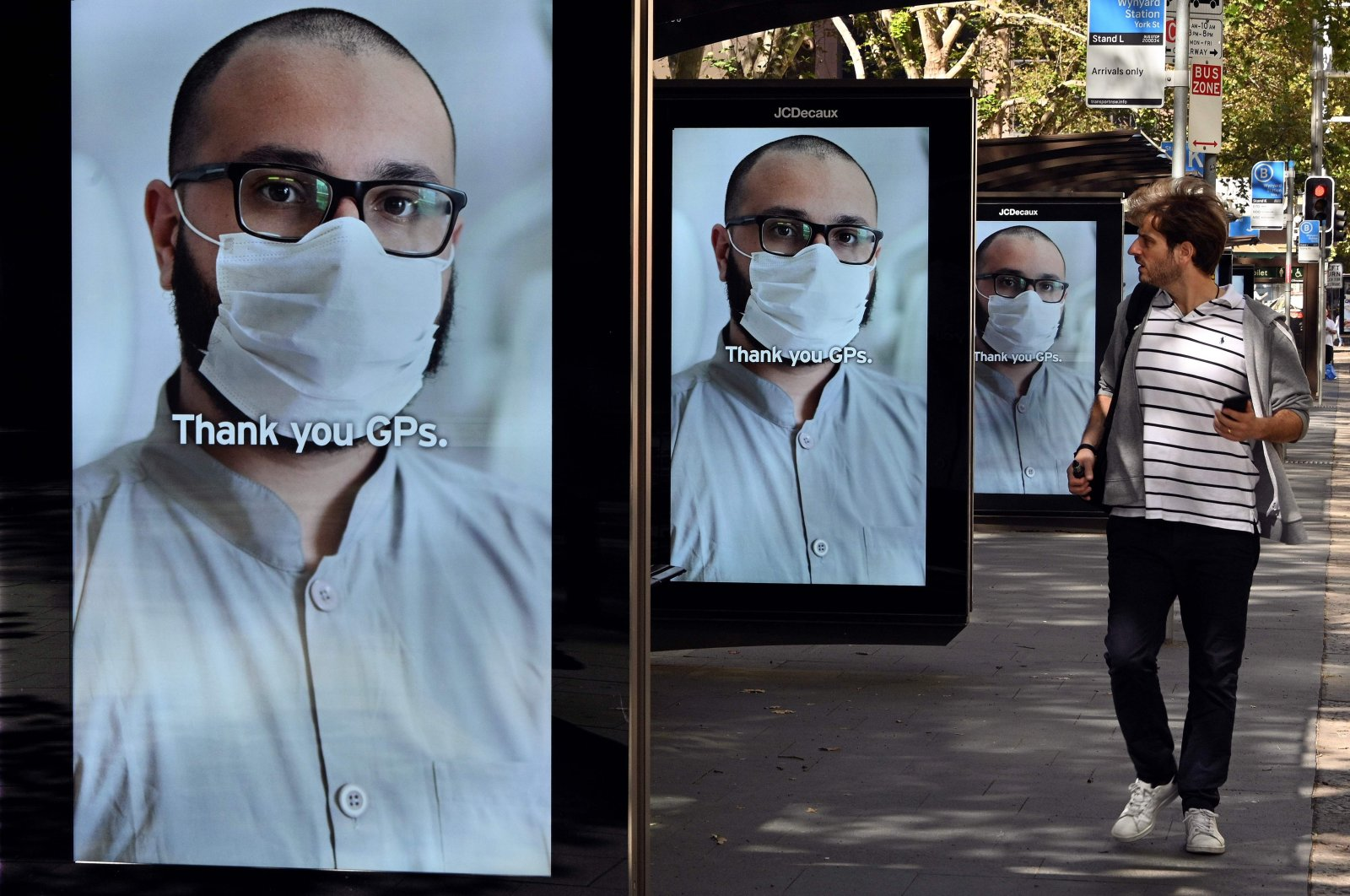 A man walks past bus stop advertising boards displaying thank you messages to health workers in response to the COVID-19 coronavirus outbreak, in Sydney on April 15, 2020. (AFP Photo)